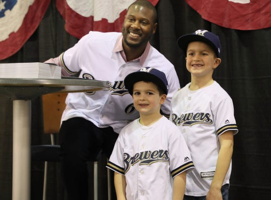 Milwaukee Brewer Lorenzo Cain poses with Cason Schur, 4, (center) and his brother Beau Schur, 7,  of Wauwatosa at the Milwaukee Brewers On Deck fan event.