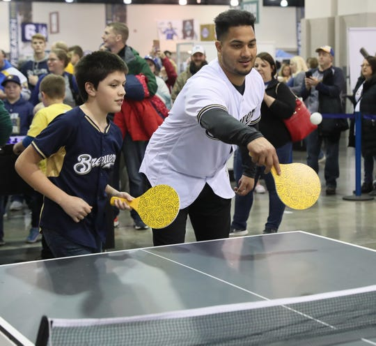 Tyler Bente, 12, of Campbellsport plays pingpong with Jhoulys Chacin (right) at the Milwaukee Brewers On Deck fan event.