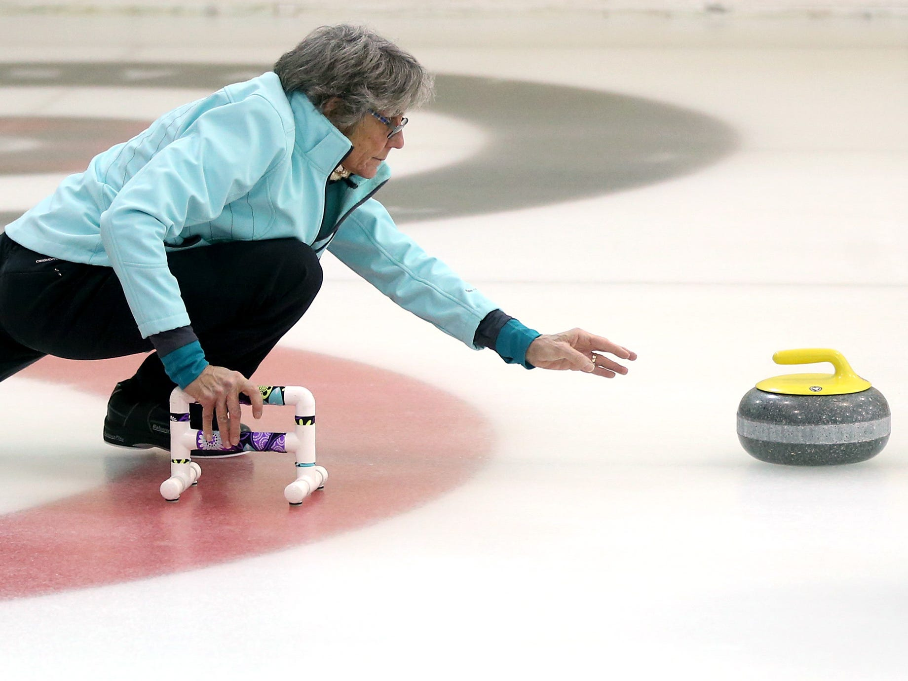 Elaine Koepke of the Milwaukee Curling Club starts a stone's slide during the Wauwatosa Curling Club's 60th annual Badger Women's Bonspiel at the Mueller Building in Hart Park on Jan. 25.