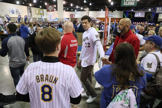 Milwaukee Brewers outfielder Christian Yelich was surrounded by adoring fans everywhere he went at the Brewers On Deck event. Security staff members help him move through the venue after an interview.