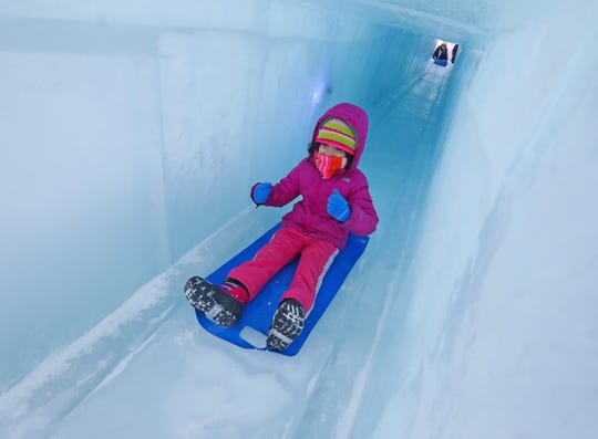 Six-year-old Kaylee Thomas, of Aurora, Illinois, slides down an ice tunnel. She was with her mother, Christina Thomas, at the Ice Castles.
