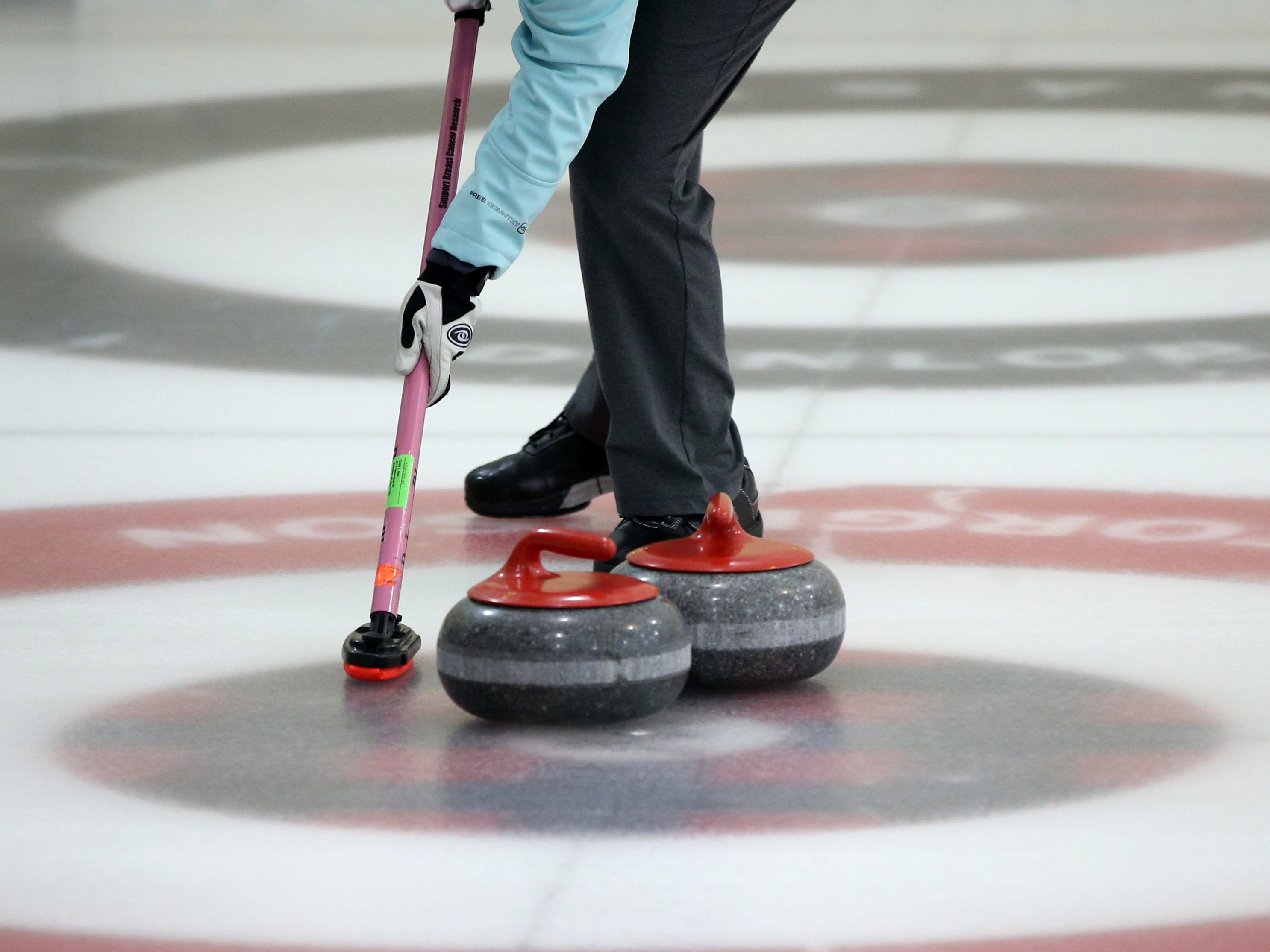 A player sweeps the ice to control the speed and direction of a stone during the Wauwatosa Curling Club's 60th annual Badger Women's Bonspiel at the Mueller Building in Hart Park on Jan. 25.