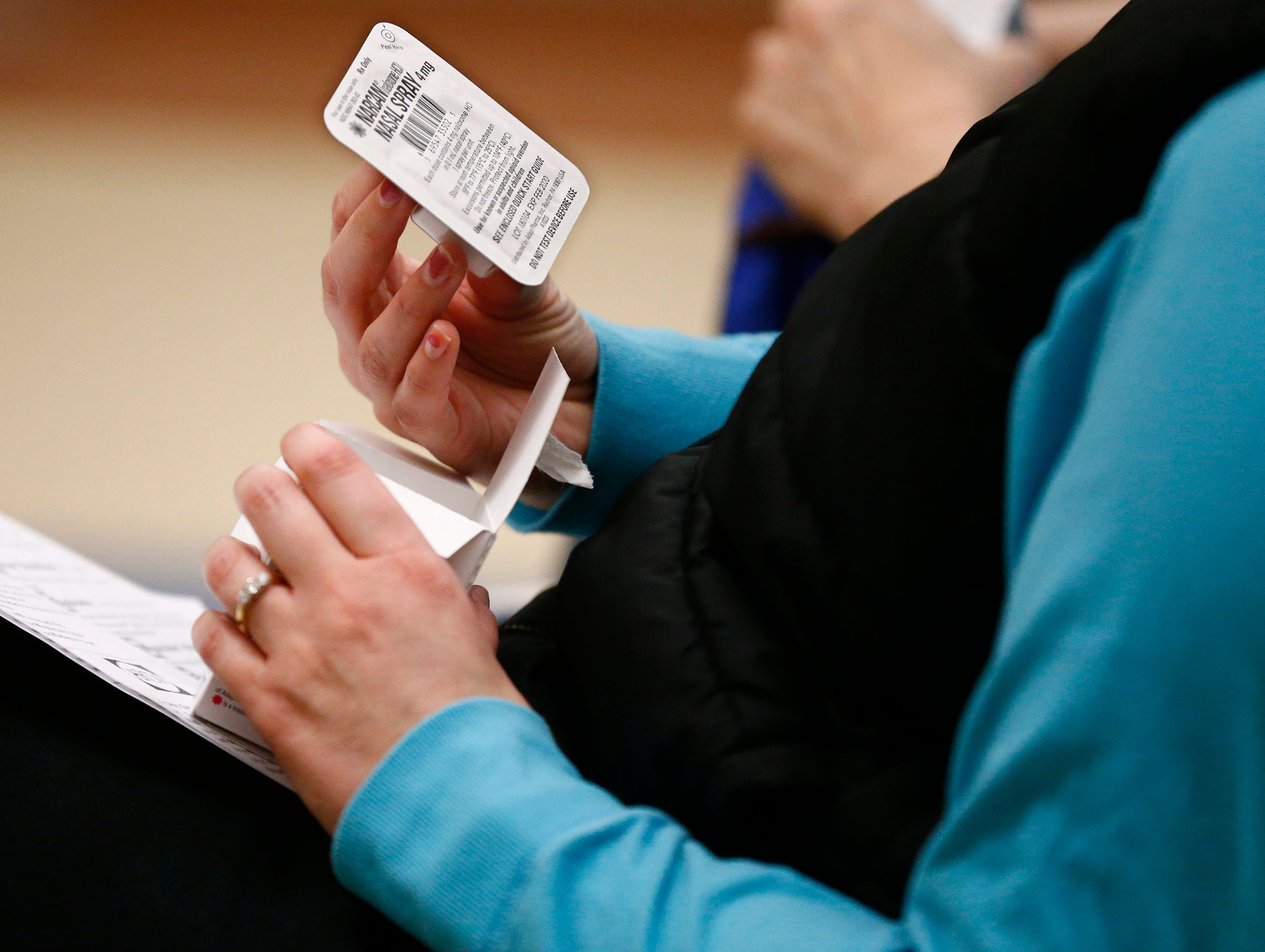 A student examines the nasal Narcan issued to a dozen students during an opiate overdose prevention workshop at the Salvation Army's Greenfield facility on Jan. 24.