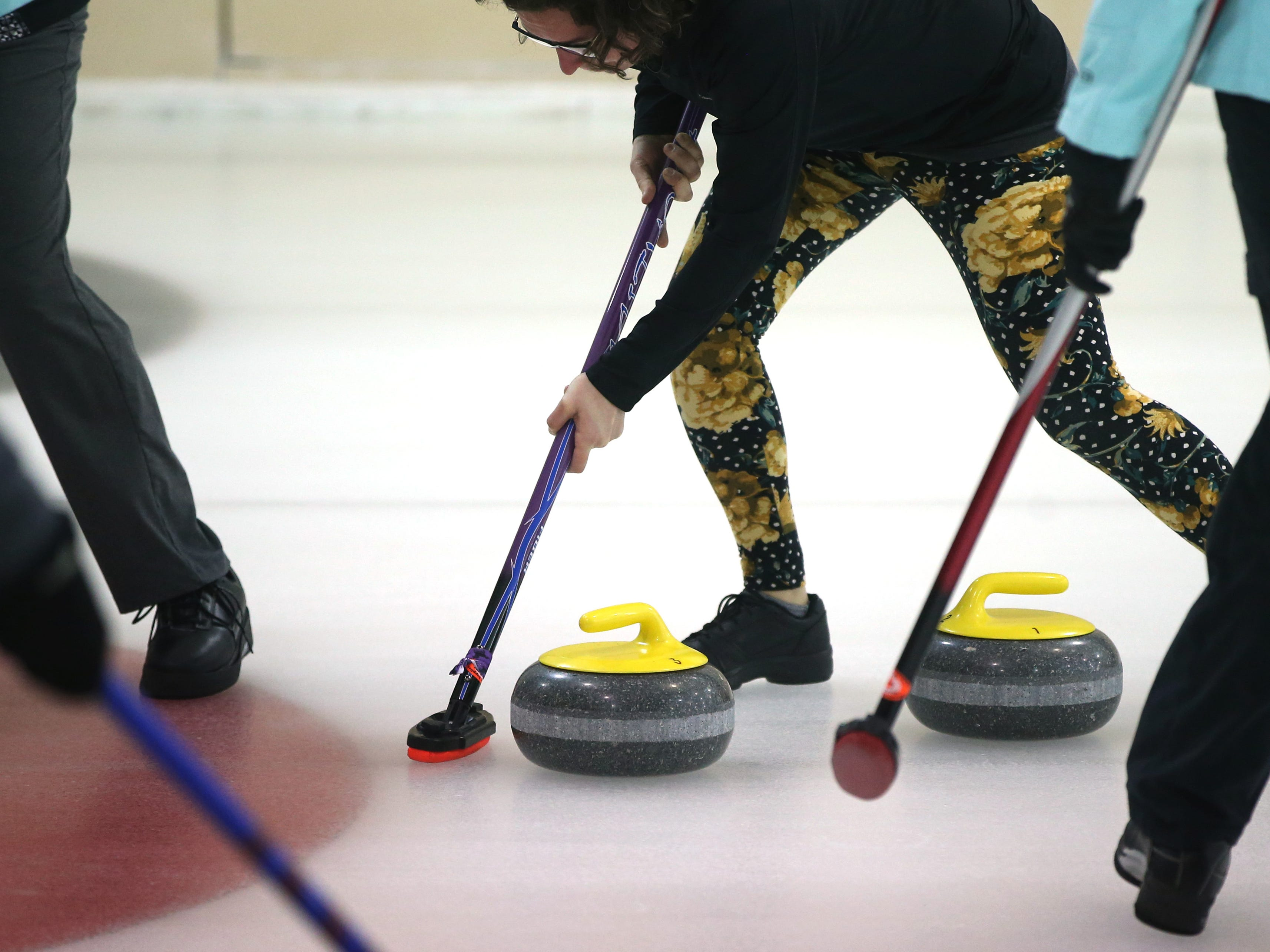 Players sweep the ice to control the speed and direction of a stone during the Wauwatosa Curling Club's 60th annual Badger Women's Bonspiel at the Mueller Building in Hart Park on Jan. 25.
