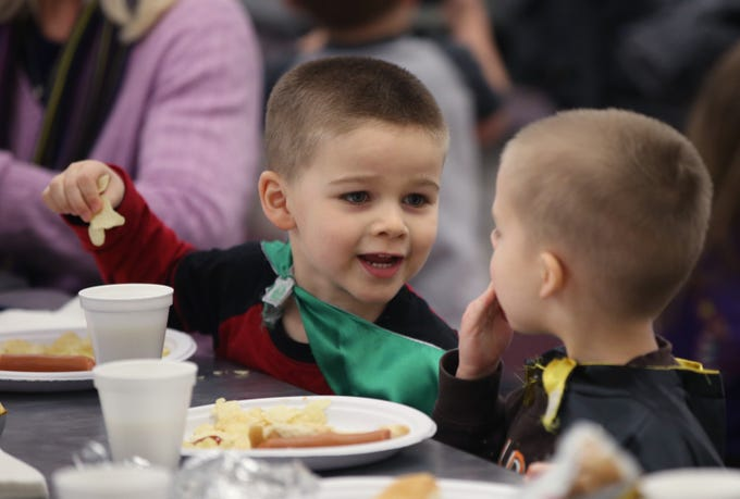 Henry (left) and Liam Wold dine on kid-friendly hot dogs during the annual Menomonee Falls Optimist Club's Chili Dinner at Menomonee Falls High School on Jan. 25.