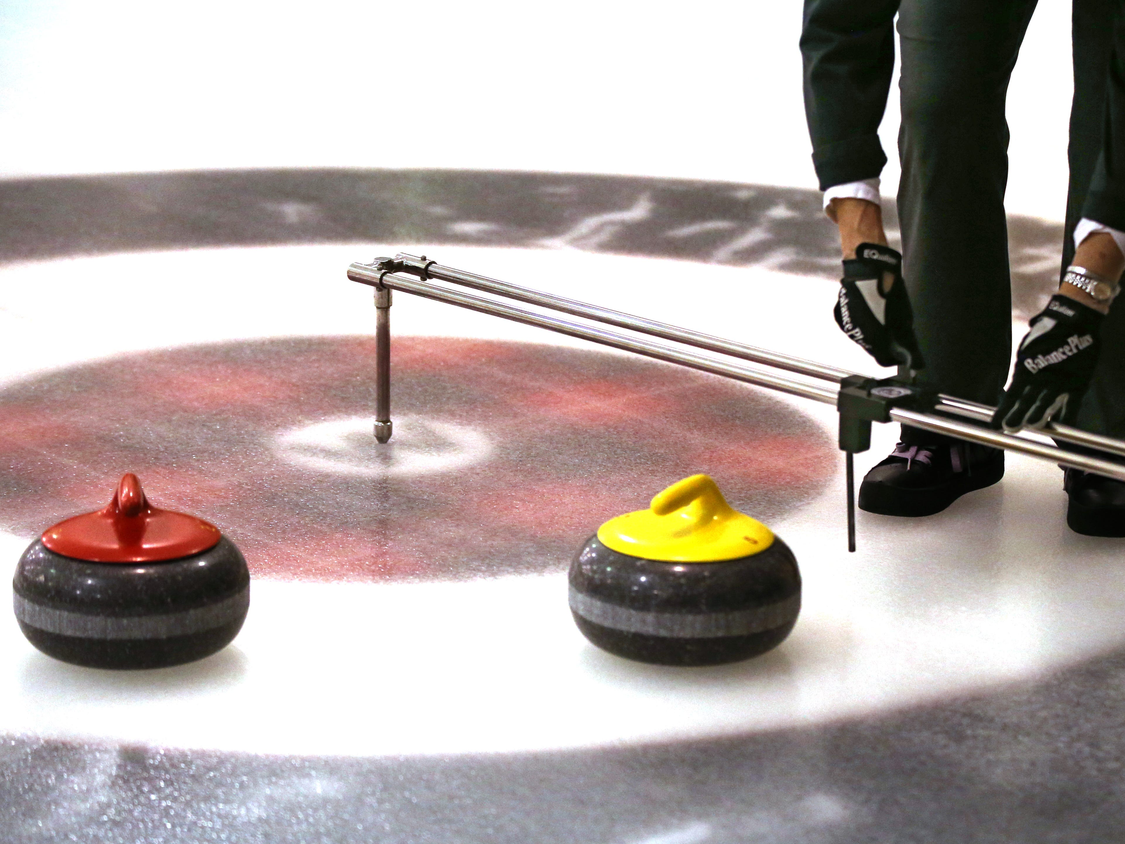 A player uses a special guage to score two stone too close to score by eye during the Wauwatosa Curling Club's 60th annual Badger Women's Bonspiel at the Mueller Building in Hart Park on Jan. 25.