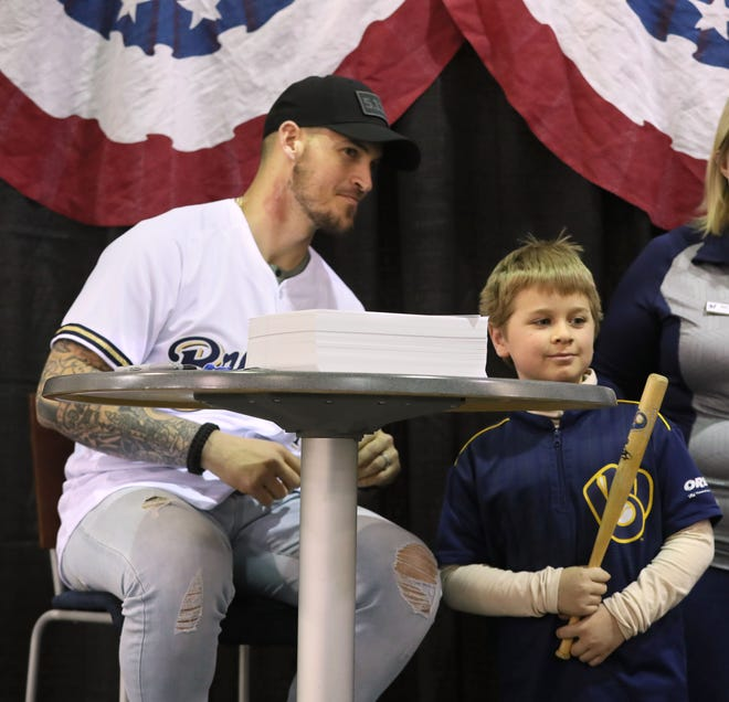 Brewers Yasmani Grandal poses for a photo with Christopher Hanson, 8, of Milwaukee after signing an autograph for him.
