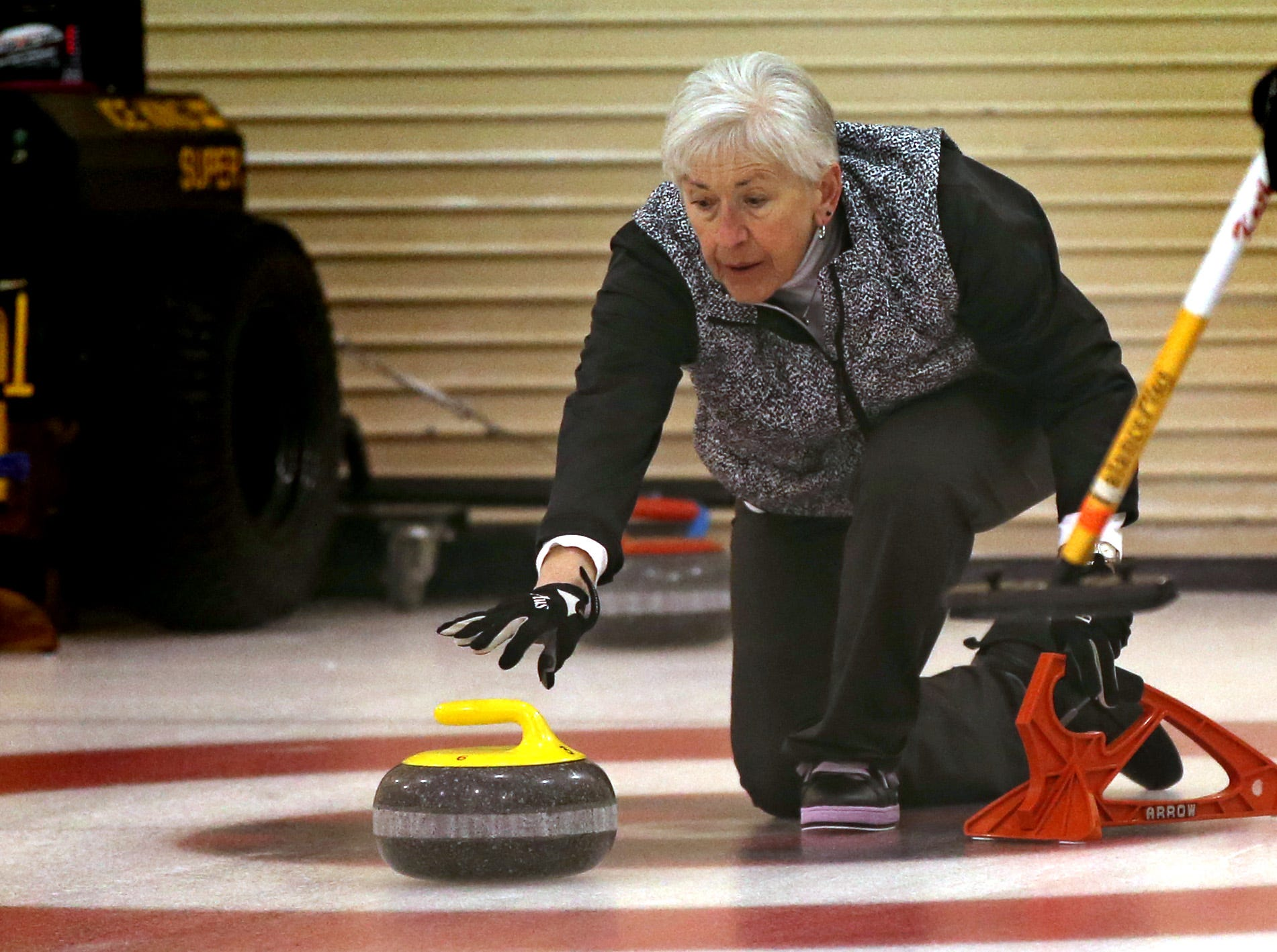 Carol Stevenson of the Kettle Moraine Curling Club starts a stone's slide during the Wauwatosa Curling Club's 60th annual Badger Women's Bonspiel at the Mueller Building in Hart Park on Jan. 25.