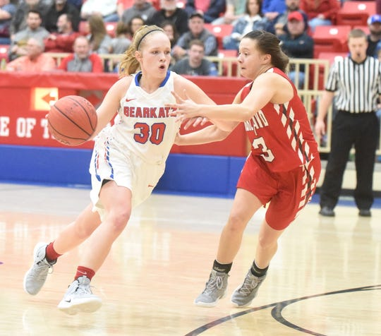 Melbourne's Josie Roark drives to the basket against Highland's Briley Pena on Saturday night.