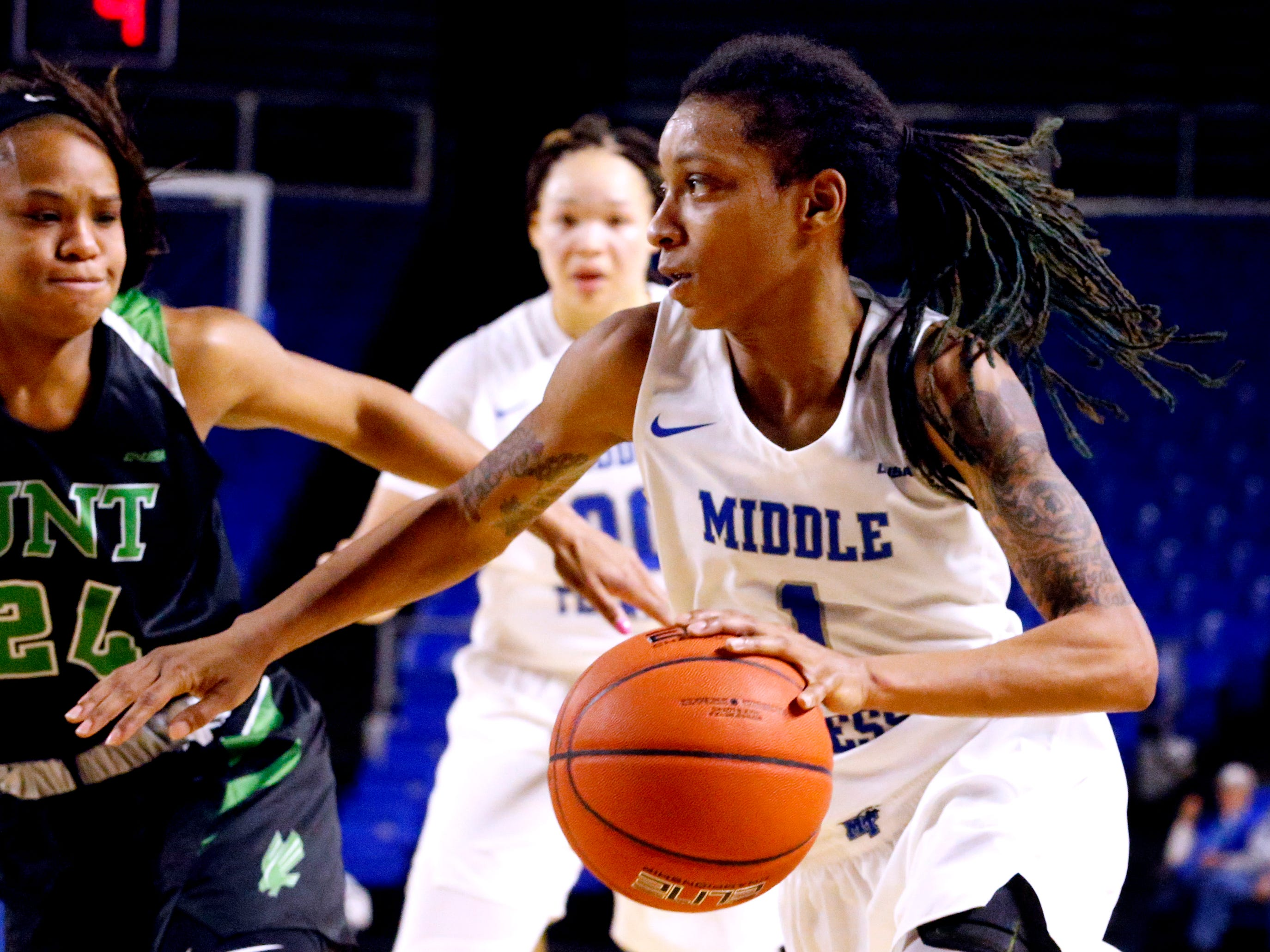 MTSU's guard A'Queen Hayes (1) drives to the basket as North Texas' guard Trena Mims (24) comes in to guard her on Saturday Jan. 26, 2019.