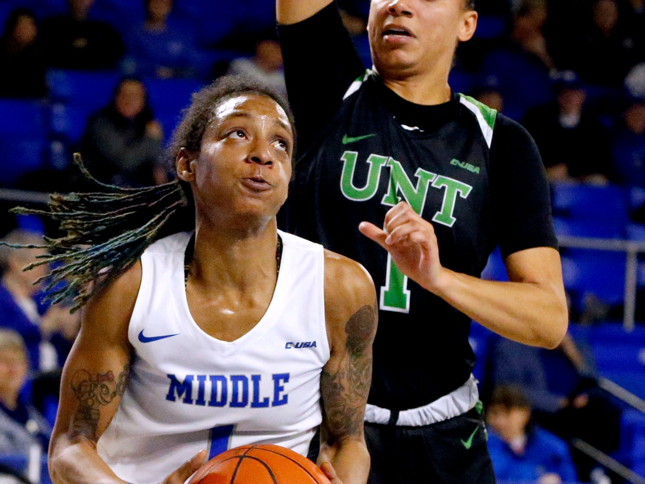MTSU's guard A'Queen Hayes (1) goes to shoot the all as North Texas' guard Callie Owens (1) defends her on Saturday Jan. 26, 2019.