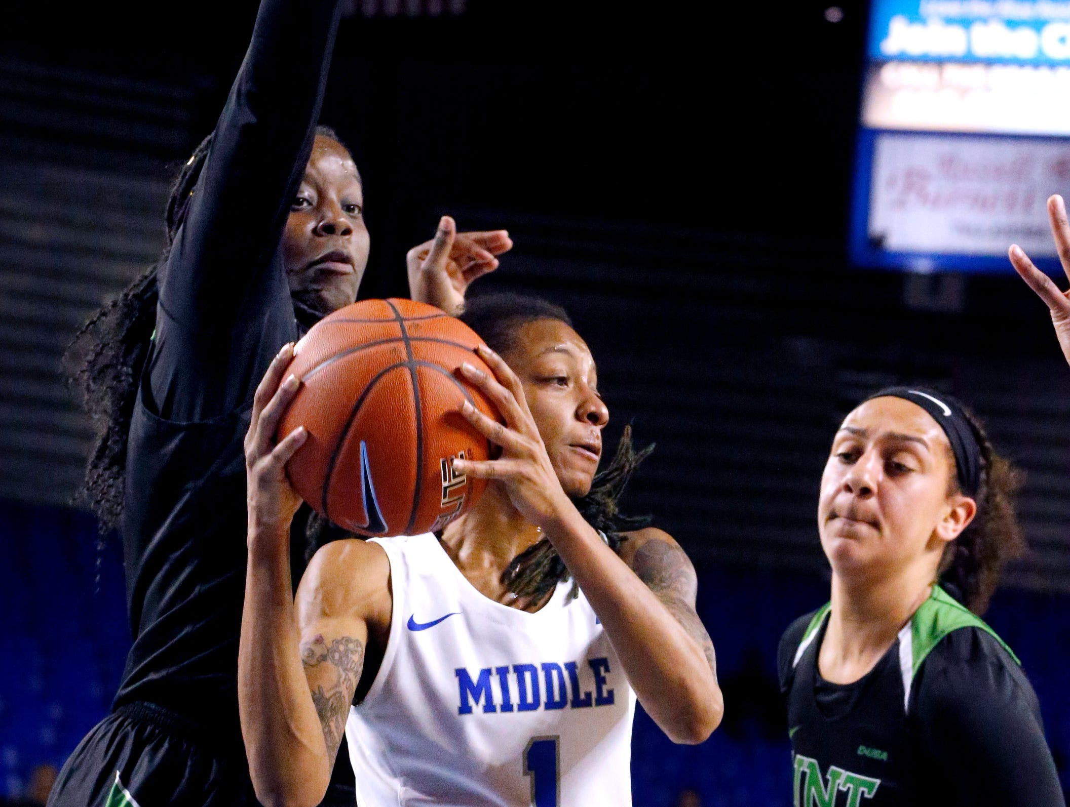 MTSU's guard A'Queen Hayes (1) looks to pass the ball as North Texas' forward/center Anisha George (42) and North Texas' forward Charlene Shepherd (11) cover her on Saturday Jan. 26, 2019.