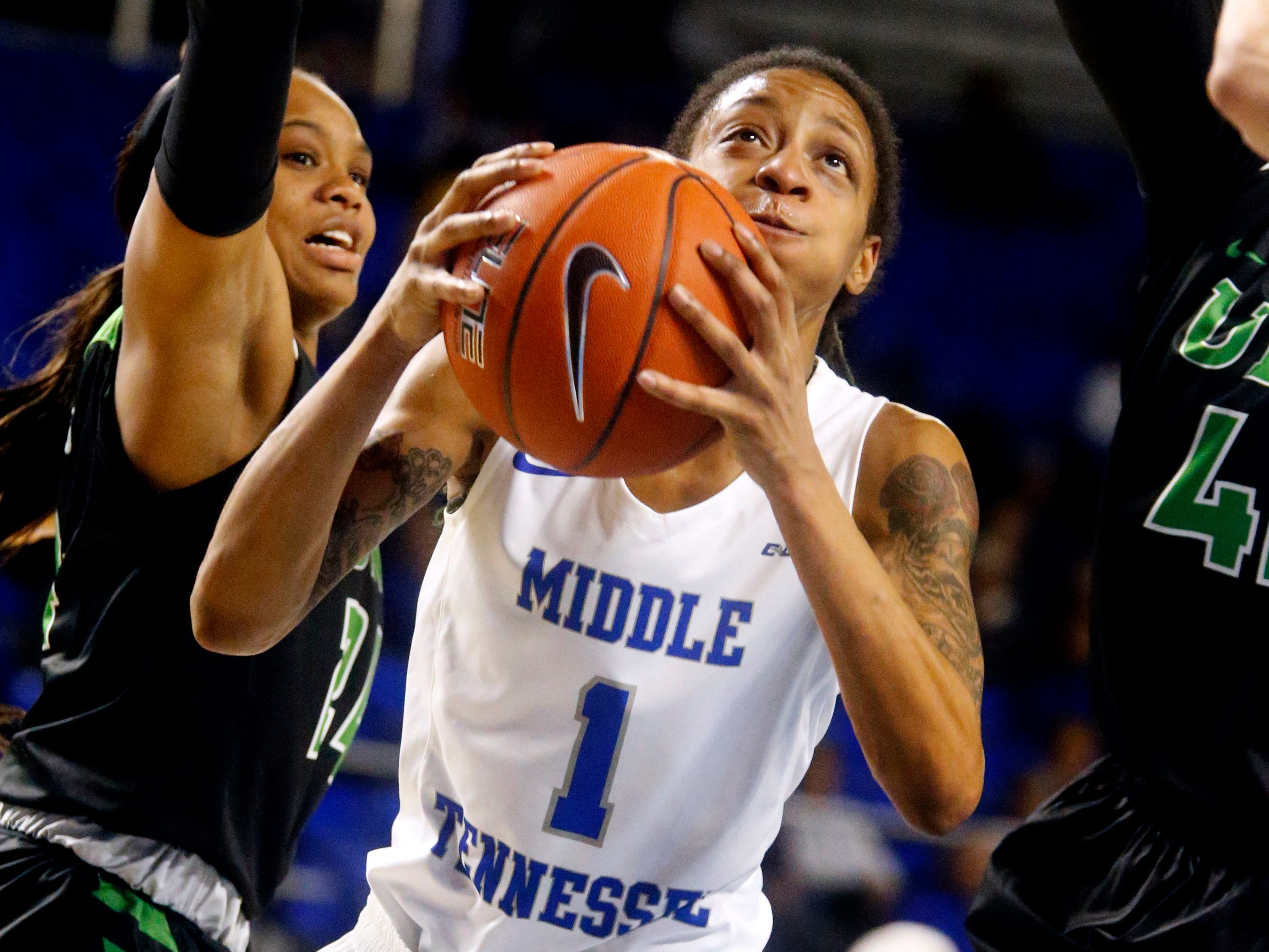 MTSU's guard A'Queen Hayes (1) shoots the ball between North Texas' guard Trena Mims (24) and  North Texas' forward/center Anisha George (42) on Saturday Jan. 26, 2019.