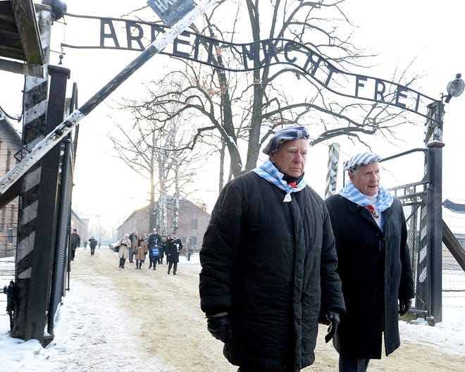 "Survivors of Auschwitz gather on the 74th anniversary of the liberation of the former Nazi German death camp in Oswiecim, Poland, on Sunday, Jan. 27, 2019. They wore striped scarves that recalled their uniforms, some with the red letter ""P,"" the symbol the Germans used to mark them as Poles. The observances come on International Holocaust Remembrance Day."