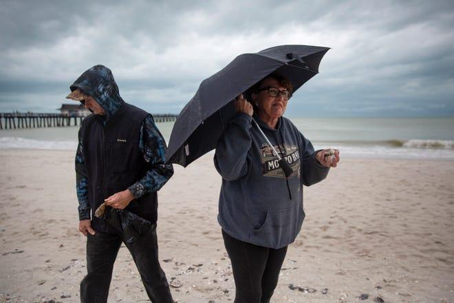 Mike Lovett and Melinda Cherko, visiting Naples from Sacramento, Calif., collect shells Sunday,  Jan. 27, 2019, near the Naples Pier.