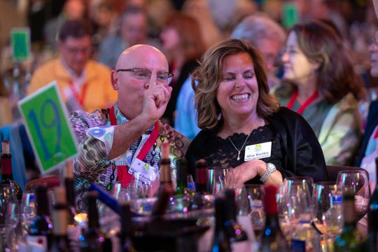 David and Alise Bartley makes a motion to the auctioneer during a bidding war at the Naples Winter Wine Festival, Saturday, Jan. 26, 2019, at the Ritz-Carlton Golf Resort in  Naples.