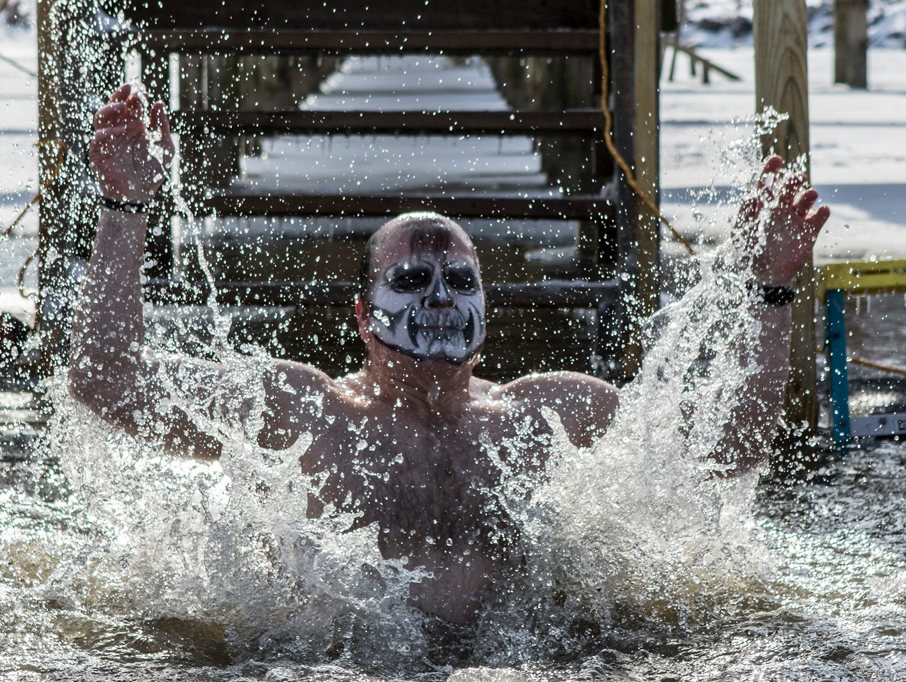 Ron Gillespie of Bexley, emerges from the water at Buckeye Lake after jumping in Sunday in 20 degree weather. Before jumping Gillespie shouted out this was the dumbest thing he'd ever done. Around 20 people walked down the pier at Buckeye Lake Winery to jump into Buckeye Lake Sunday for the annual Polar Plunge. Crowds gathered on the lake around an opening cut into the ice to cheer on those brave enough top jump.