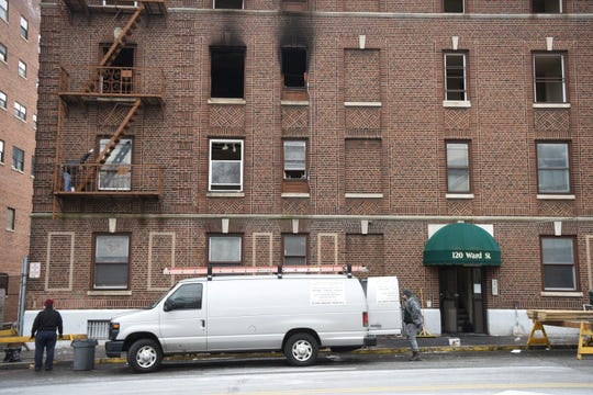 Employees from Garden State Management work to secure the building after an early-morning fire at 120 Ward St. in Paterson on Sunday, January 27, 2019, displaced residents from 11 apartments.