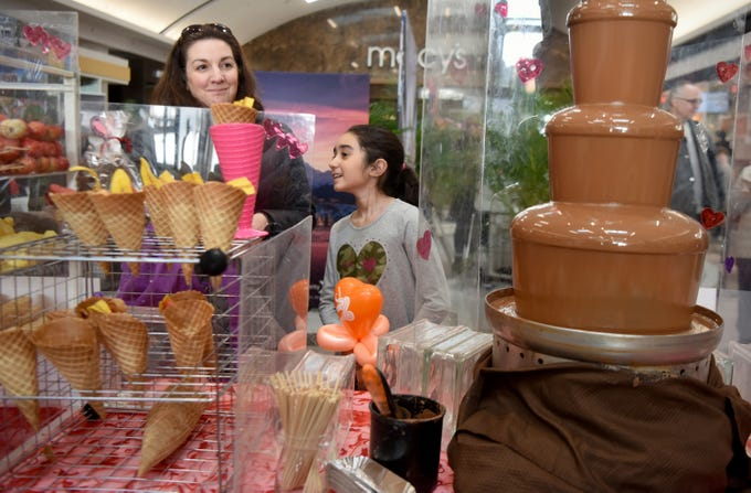 Anne Marie Astudillo of Bergenfield and her daughter, Brooke, try to decide which treat they want to cover in chocolate from the flowing fountain at the Chocolate Expo, held Sunday, January 27, 2019, at Westfield Garden State Plaza in Paramus.