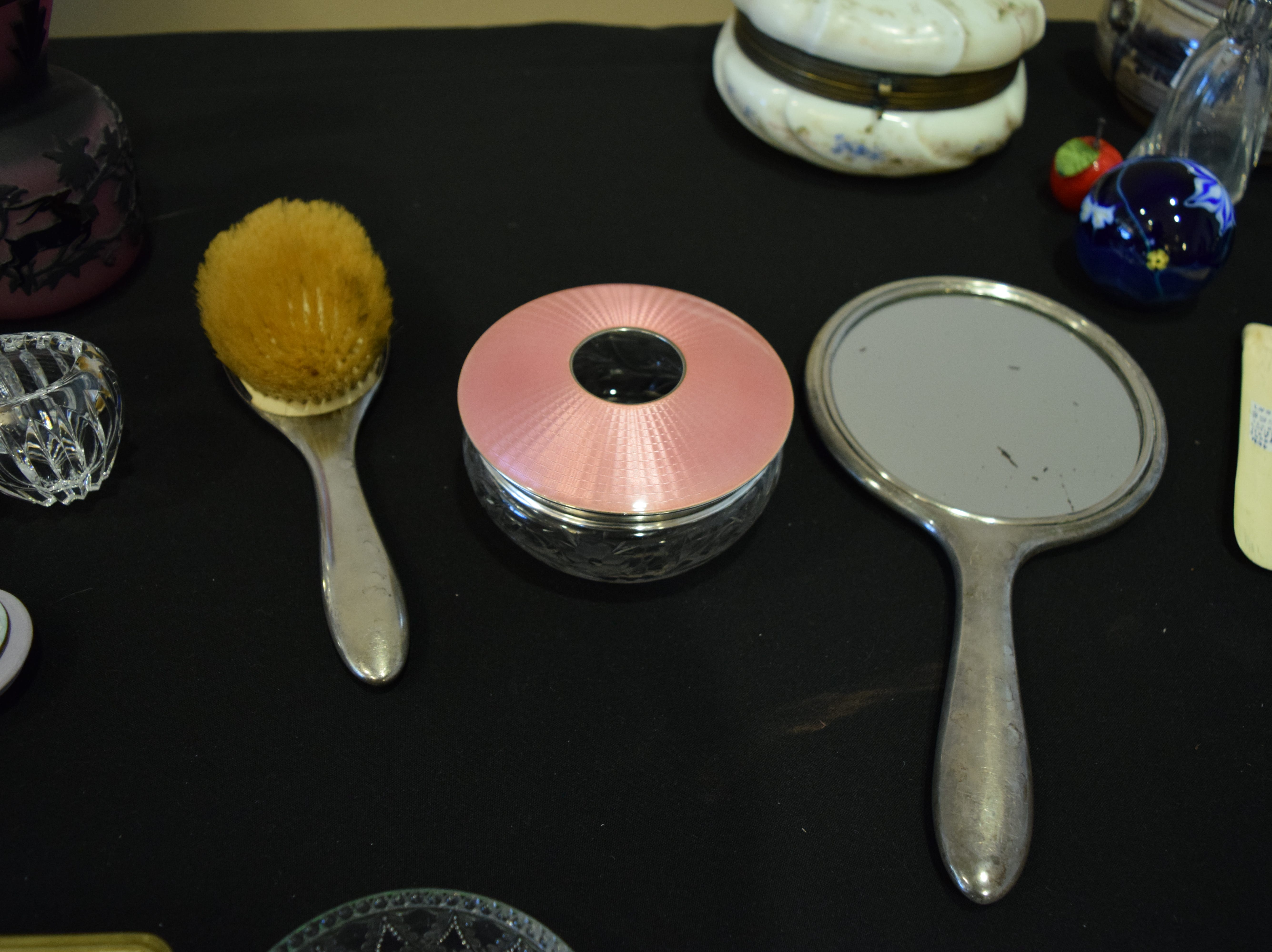This sterling silver and pink enamel beauty set is estimated to from the 1920s, or thereabouts. The art deco-inspired pieces have a guilloche pattern that was quite common at the time. The bowl in the middle is a hair receiver. Hair receivers were used in the Victorian era and even up until the 1950s. The hair would be collected from brushes and combs and used to create ratts (small balls of hair) that could be used to create volume and fullness in a hairstyle. The extraneous hair was also sometimes used as stuffing for pin cushions and small pillows. — Antiques Treasures Show at the Farm and Ranch Heritage Museum, Jan. 26, 2019.