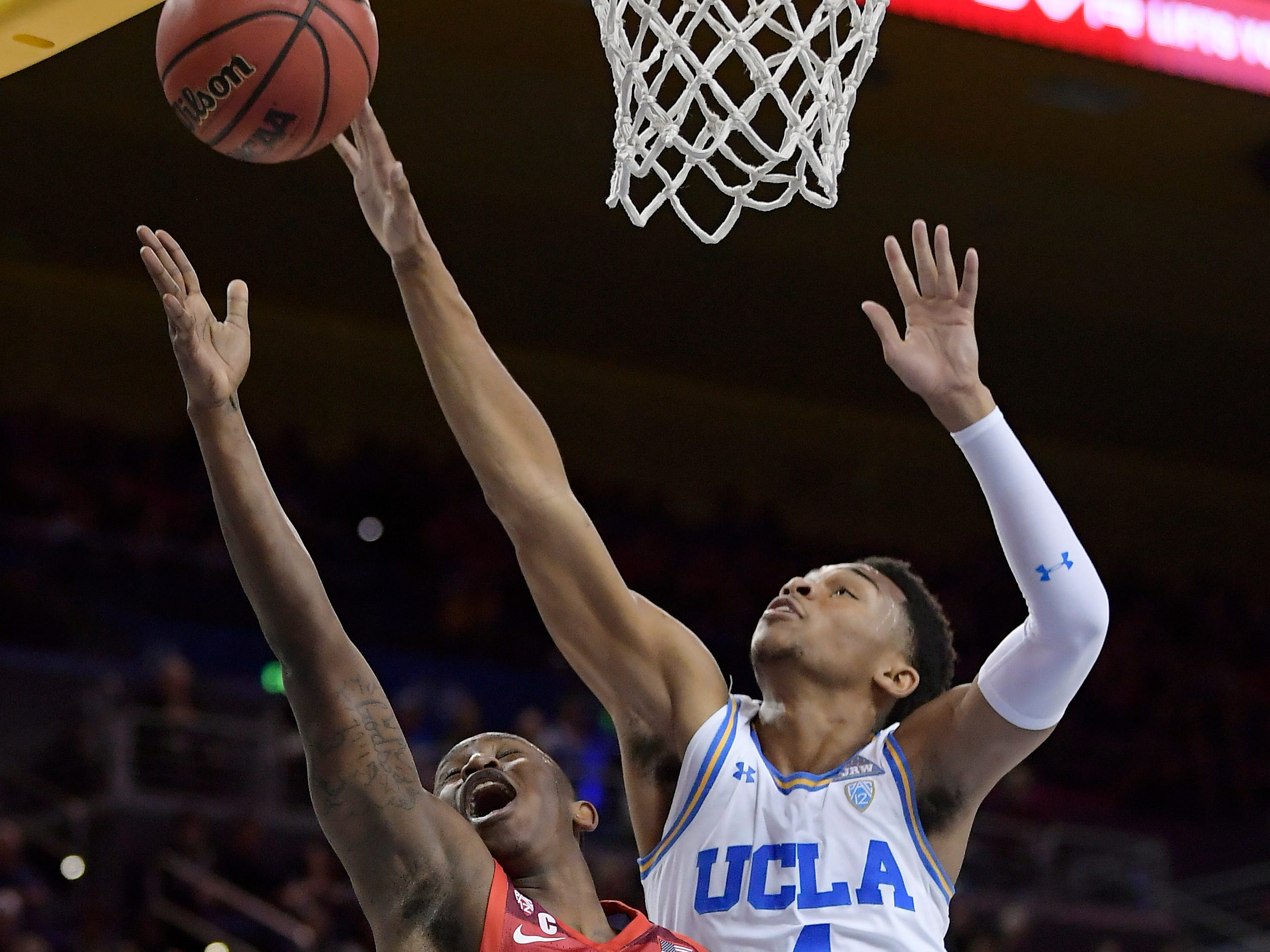 Arizona guard Justin Coleman, left, shoots as UCLA guard Jaylen Hands defends during the first half of an NCAA college basketball game Saturday, Jan. 26, 2019, in Los Angeles.