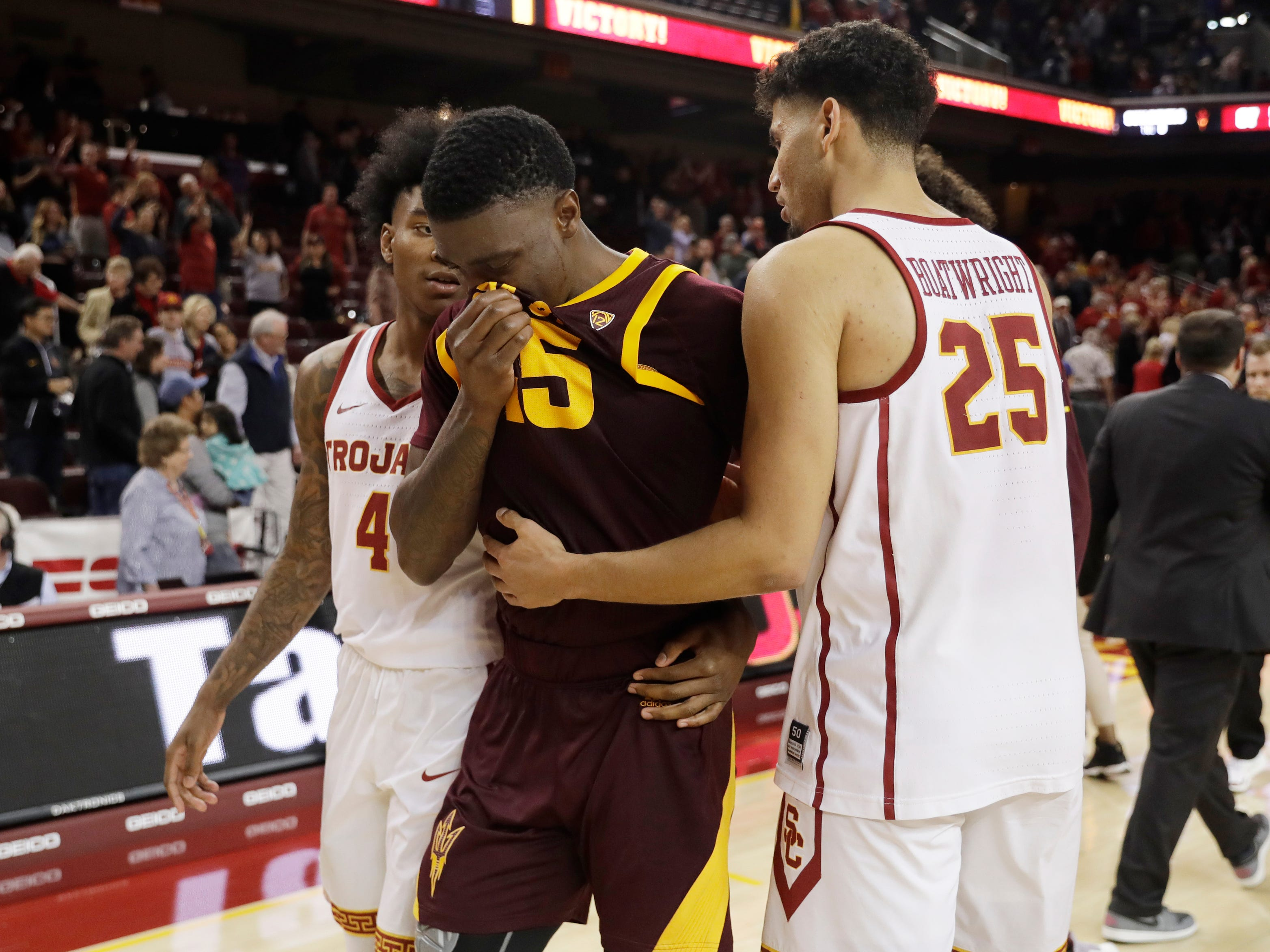 Arizona State forward Zylan Cheatham, center, is consoled by Southern California's Bennie Boatwright, right, and Kevin Porter Jr. (4) after Southern California's win during an NCAA college basketball game Saturday, Jan. 26, 2019, in Los Angeles.