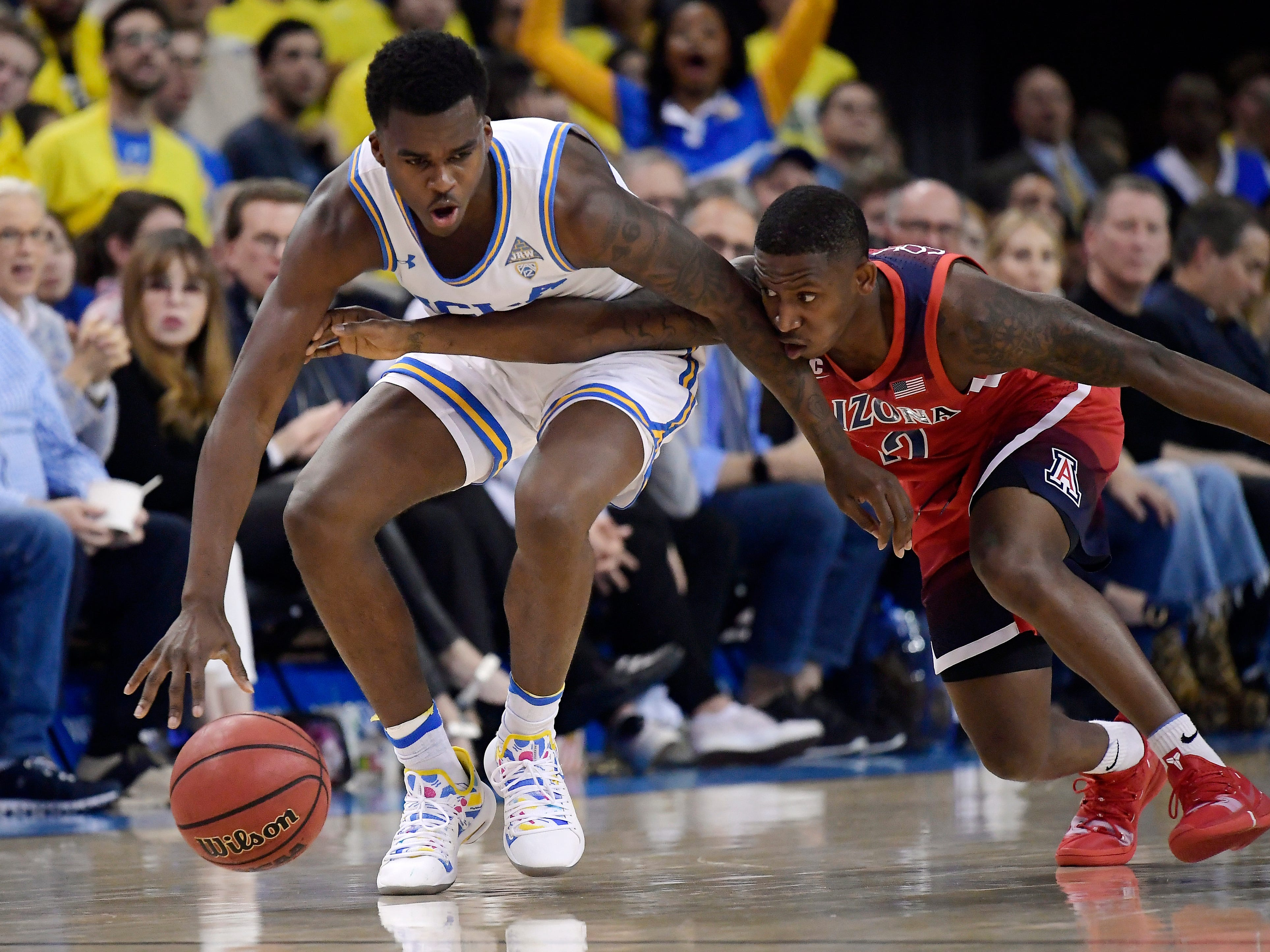 Arizona guard Justin Coleman, right, reaches for the ball against UCLA guard Kris Wilkes during the first half of an NCAA college basketball game Saturday, Jan. 26, 2019, in Los Angeles.