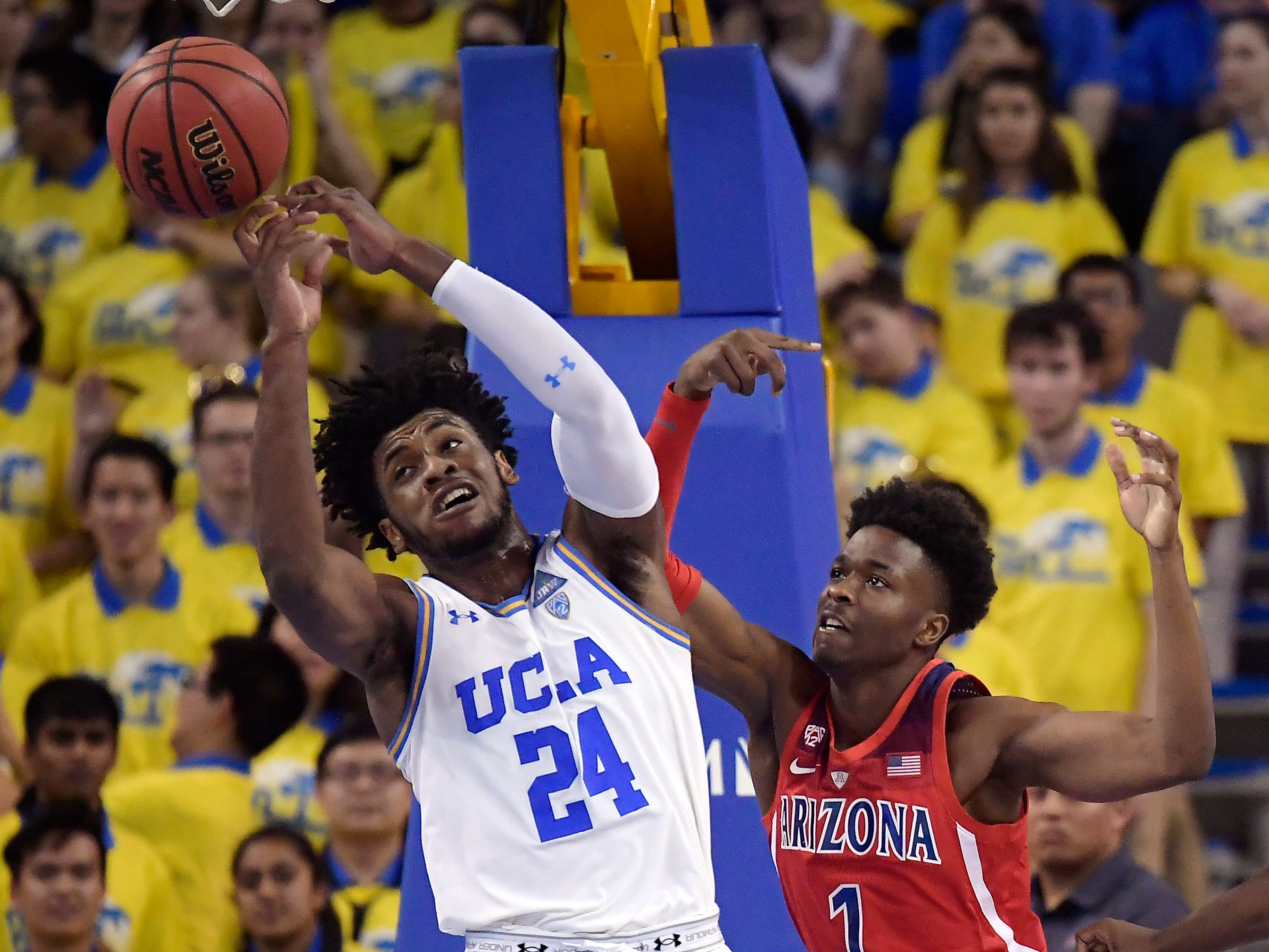 UCLA guard Jalen Hill, left, and Arizona guard Devonaire Doutrive reach for a rebound during the second half of an NCAA college basketball game Saturday, Jan. 26, 2019, in Los Angeles. UCLA won 90-69.