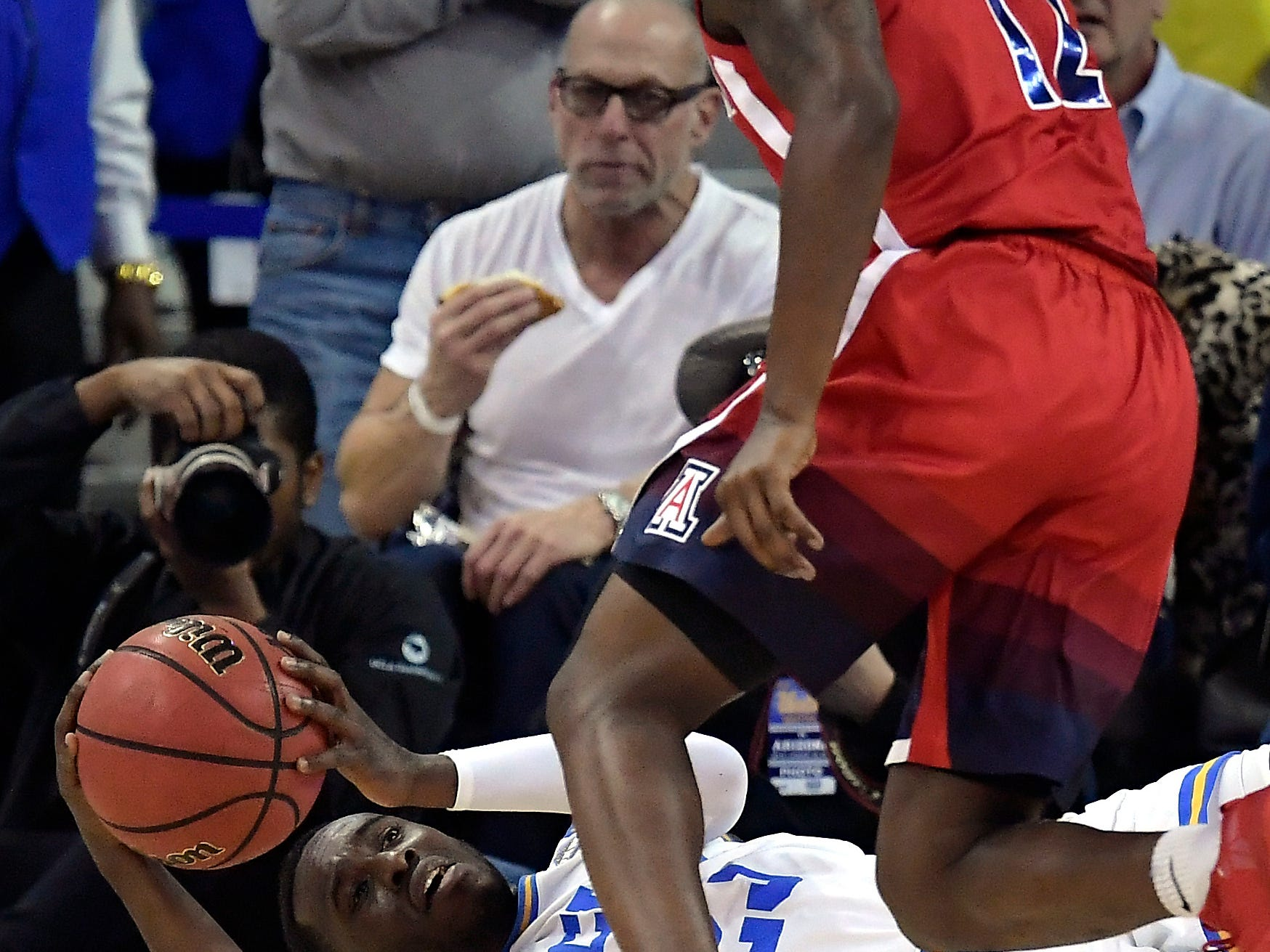 UCLA guard Prince Ali tries to pass the ball after falling while under pressure from Arizona guard Justin Coleman during the first half of an NCAA college basketball game Saturday, Jan. 26, 2019, in Los Angeles.