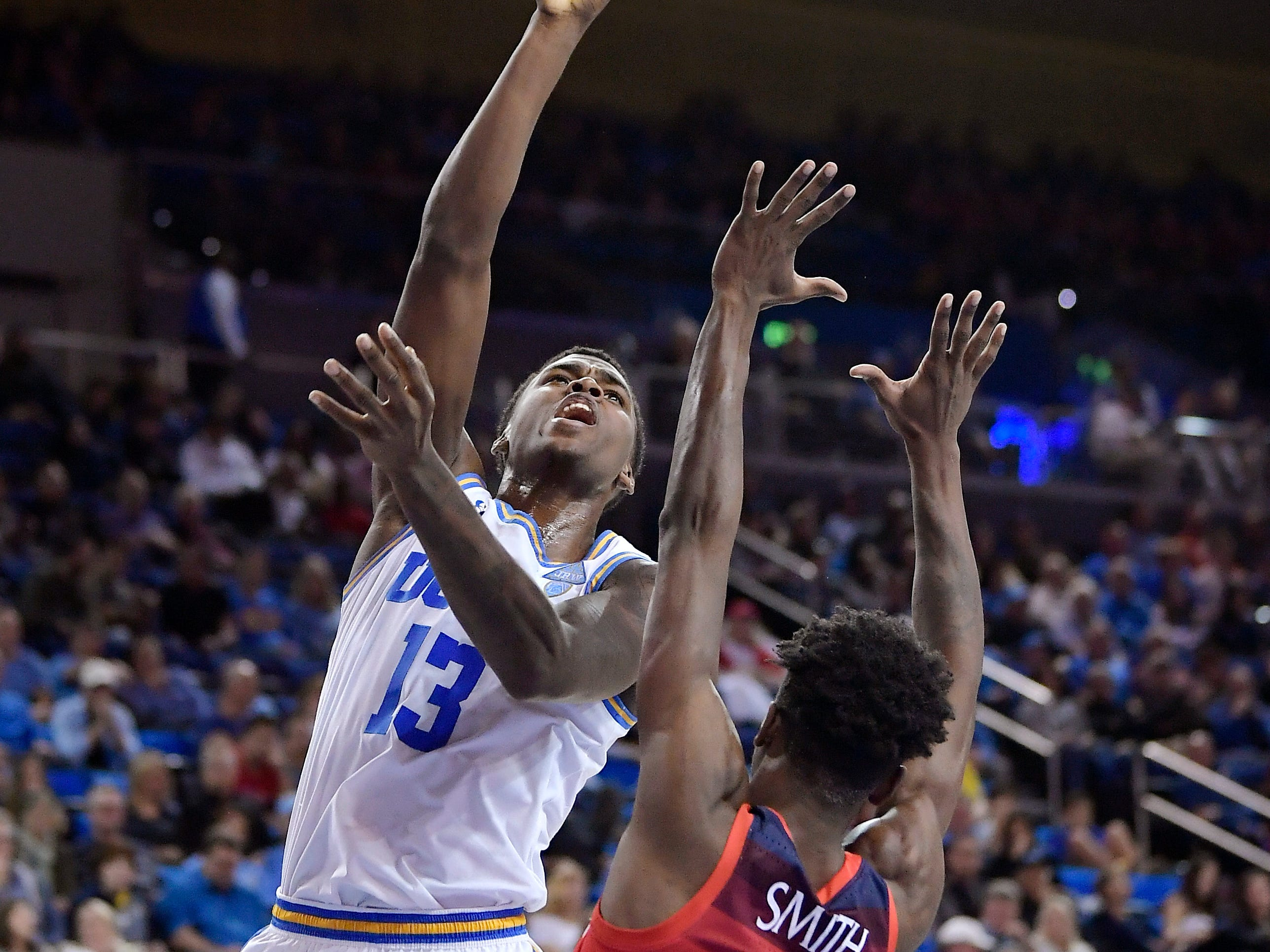 UCLA guard Kris Wilkes, left, shoots as Arizona guard Dylan Smith defends during the second half of an NCAA college basketball game Saturday, Jan. 26, 2019, in Los Angeles. UCLA won 90-69.