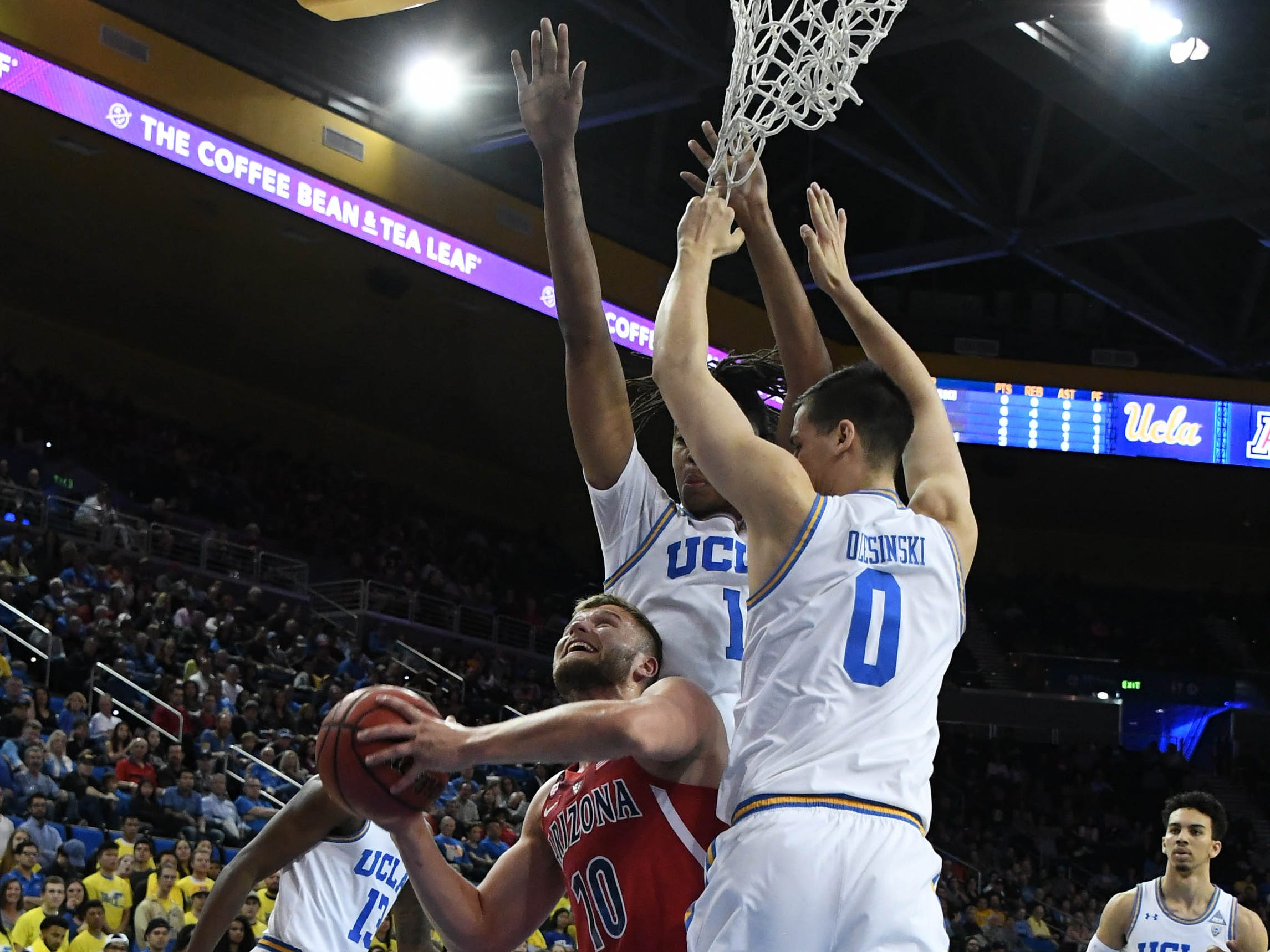 Jan 26, 2019; Los Angeles, CA, USA; Arizona Wildcats forward Ryan Luther (10) shoots between UCLA Bruins forward Alex Olesinski (0) and center Moses Brown (1) in the first half at Pauley Pavilion.