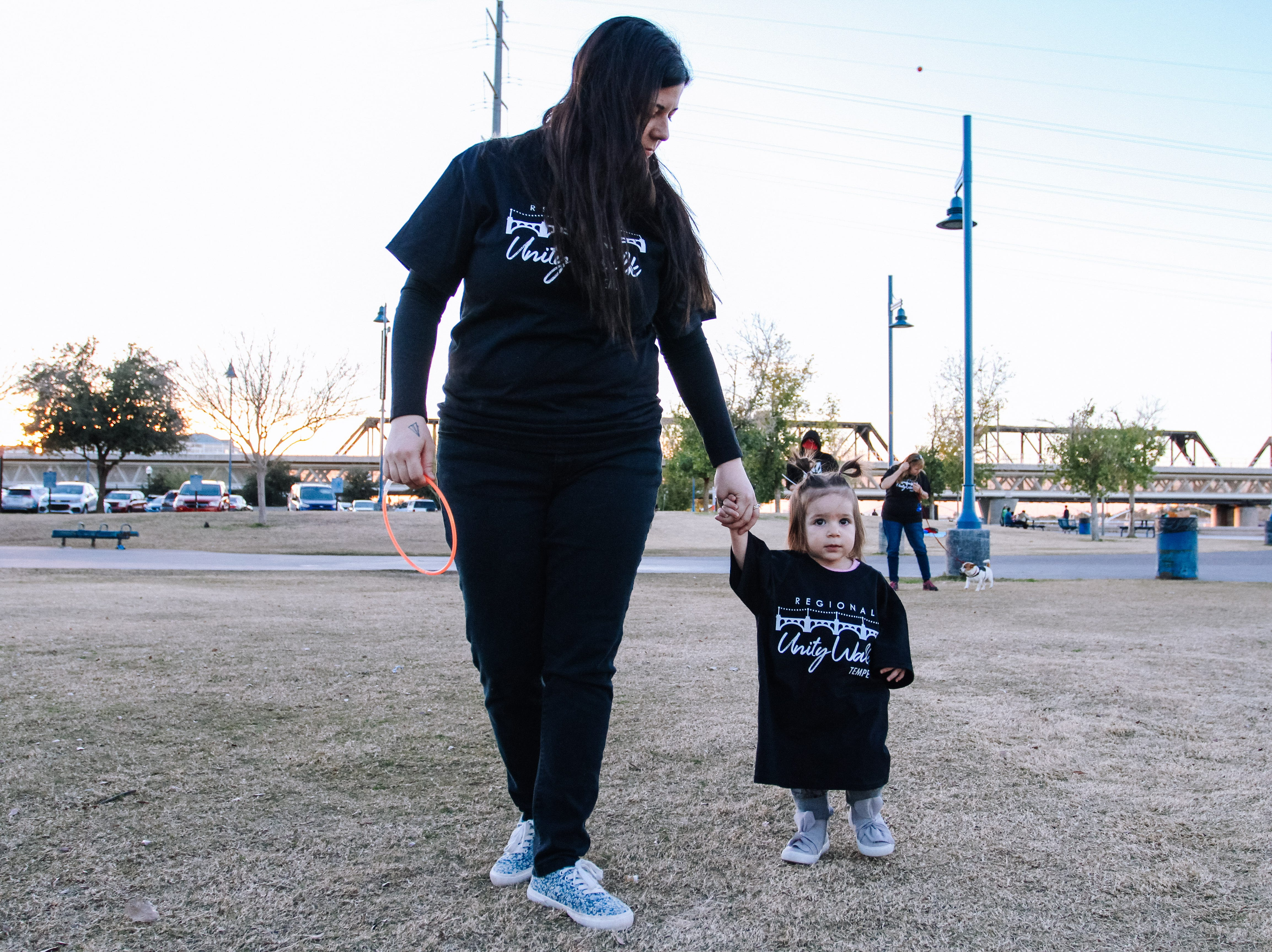 Samantha Jones, a teacher at Tempe High School, walks with her daughter at the Unity Walk 2019 at Tempe Beach Park, in Tempe, Arizona on Saturday, Jan. 26, 2019.