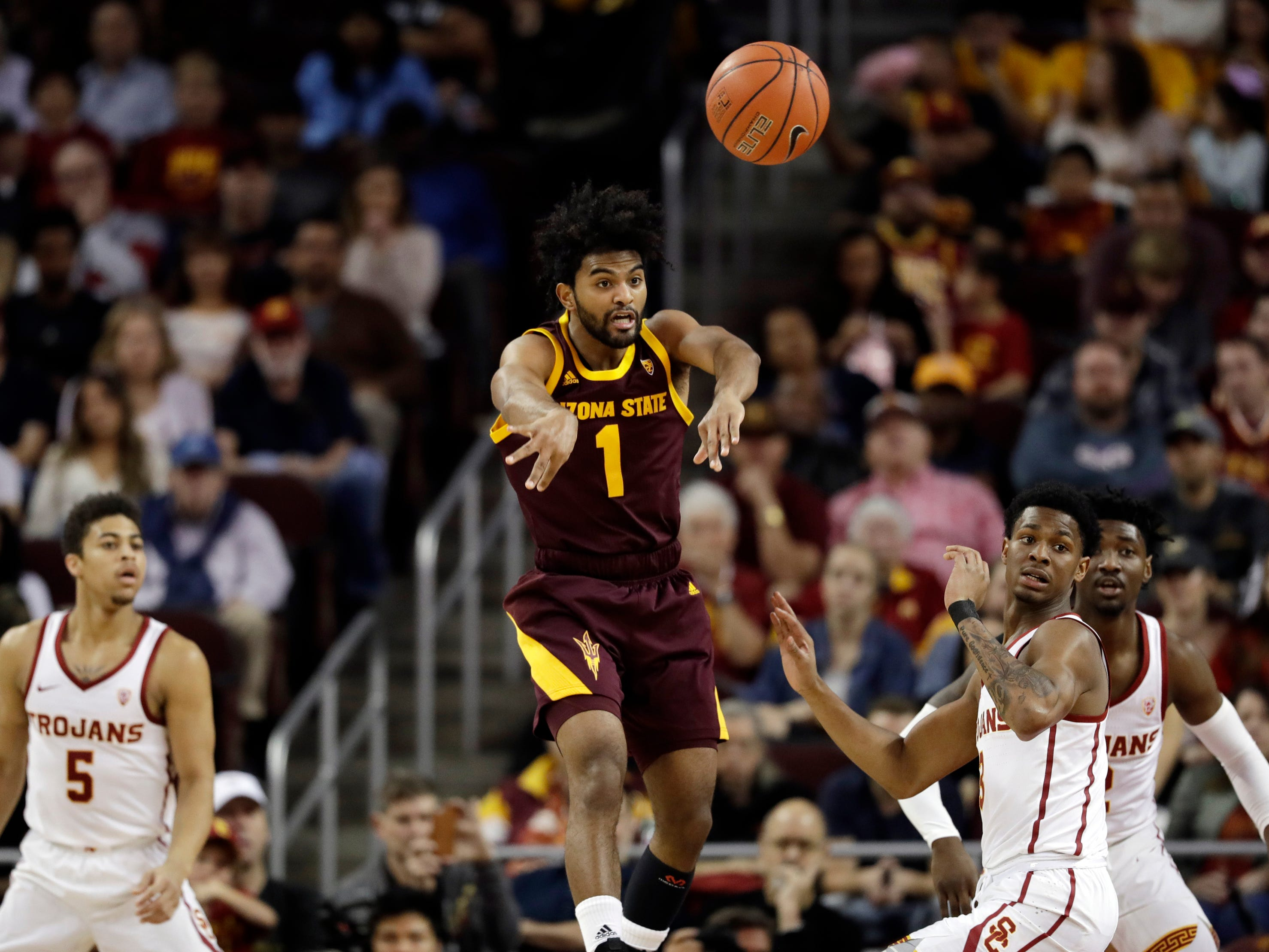 Arizona State guard Remy Martin (1) passes as he is pressured by Southern California defenders during the first half of an NCAA college basketball game Saturday, Jan. 26, 2019, in Los Angeles.