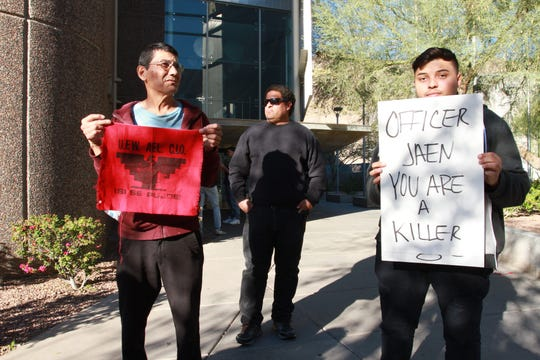 Andy Hernandez and Victor Grijalva hold signs during a protest seeking justice for 14-year-old Antonio Arce at Tempe Police Department. Arce was fatally shot on Jan. 15 by a Tempe officer responding to a call of a suspicious vehicle used in a burglary.