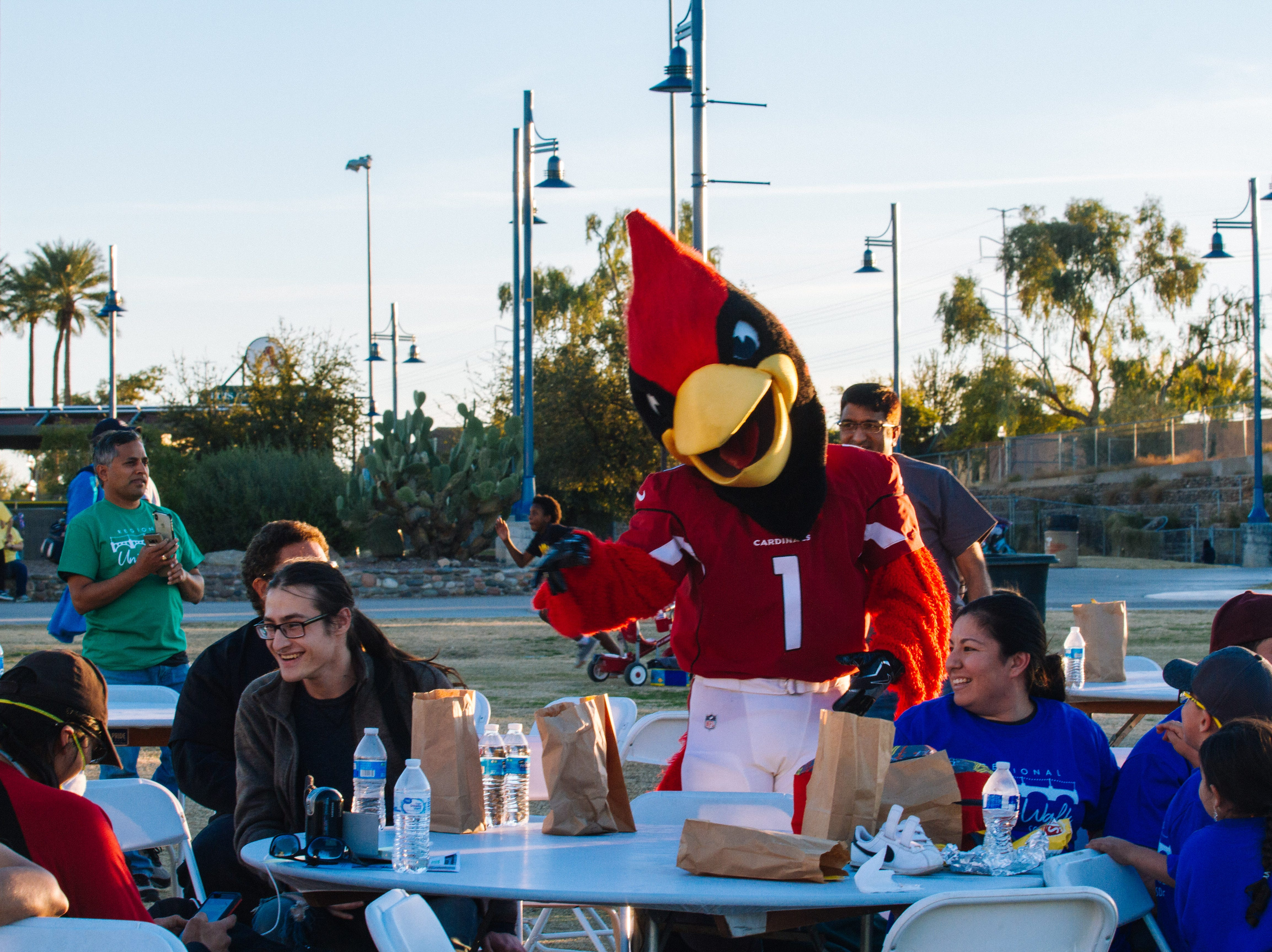 Big Red takes photos with people at the Unity Walk 2019 at Tempe Beach Park, in Tempe, Arizona on Saturday, Jan. 26, 2019.