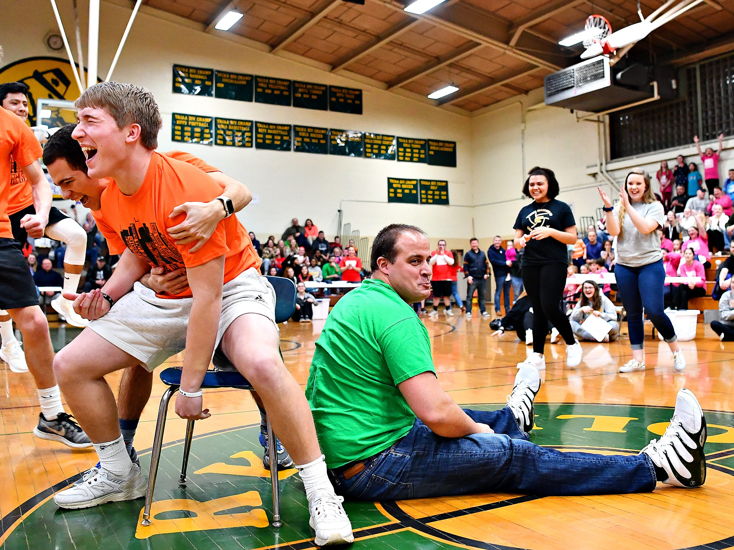 York Catholic senior Drew Snelbaker, left, celebrates after winning the final contest in musical chairs against fifth- and sixth-grade boys' basketball coach Joe Stein, right, during Battle of the Buildings at York Catholic High School in York City, Saturday, Jan. 26, 2019. Dawn J. Sagert photo