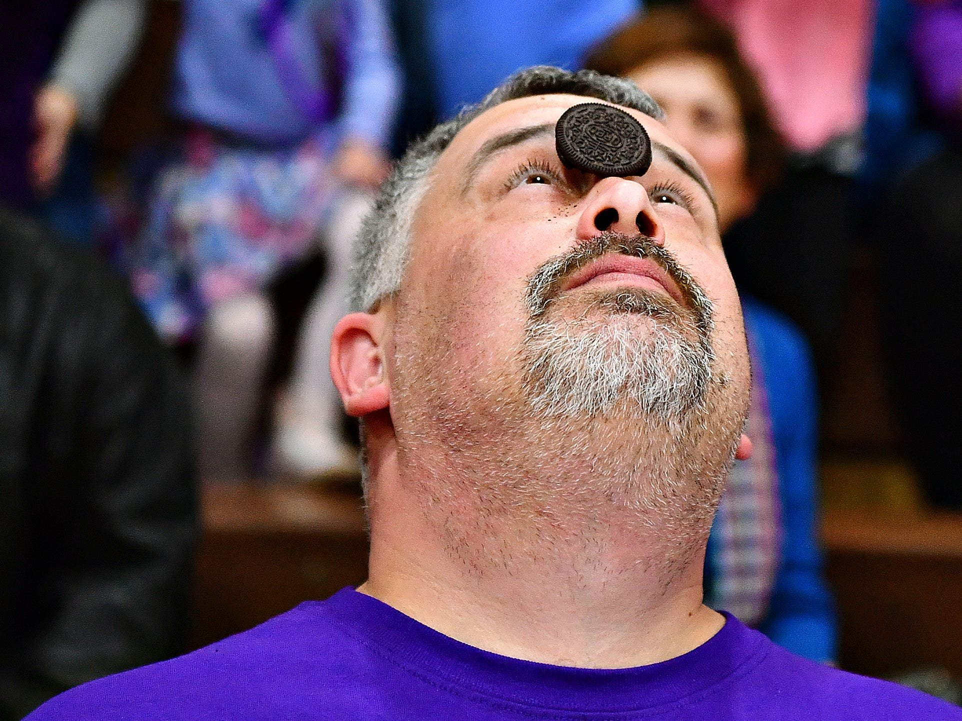 St. Rose of Lima Groundskeeper Kris Goodman repeatedly tries to get an Oreo from his forehead to his mouth, to no avail, while competing in the Cookie Monster contest during Battle of the Buildings at York Catholic High School in York City, Saturday, Jan. 26, 2019. Dawn J. Sagert photo