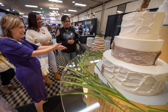 "From the left, Mary Ann Fisher, a social catering sales manager for Wyndham Garden, shows off a naked cake and a cake with burlap to Larhondsha Kollock and her future mother-in-law, Laverne Redd, during the recent York Bridal Show, Best Wedding Showcase. Naked cakes have very little icing and follow a trend of ""country, rustic, chic, bohemian,"" according to Fisher. Kollock is planning her wedding in 2020."