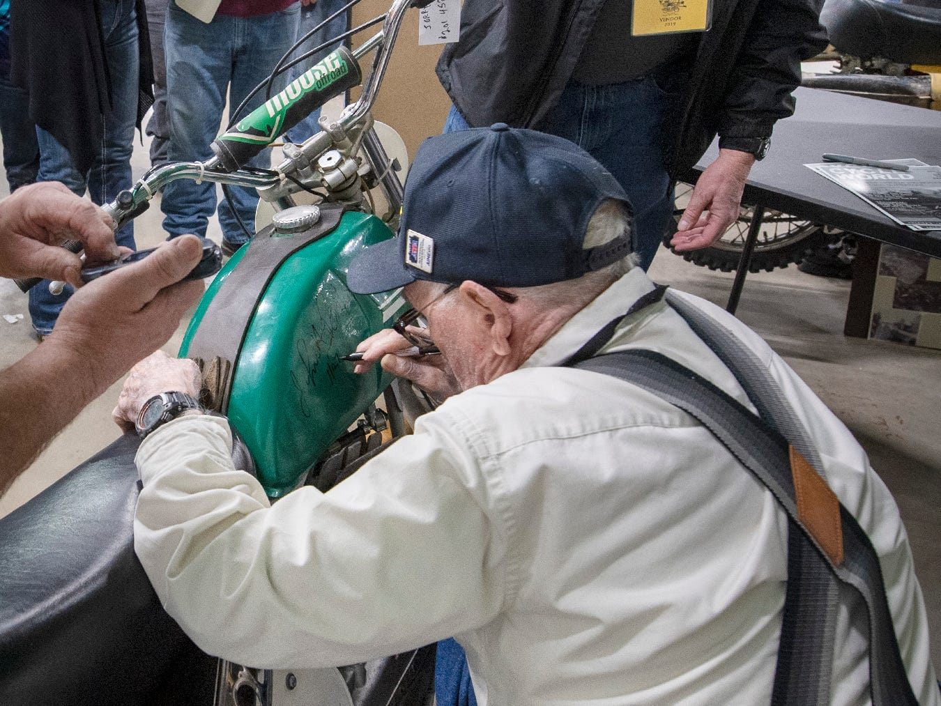 John Penton, bottom, signs a 1972 Penton motorcycle he produced for the bike's owner, Jerry Doster, during the The Potomac Vintage Riders York Swap Meet. Penton was one of the most influential figures in the development of off-road motorcycle racing in America during the 1960s and 1970s.