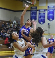 Reno's Kaitlynn Biassou shoots between Reed's Aliza Mondragon, left, Tori Baer during Tuesday's game at Reed.