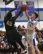 Hug's Tevin Grant has his shot blocked by McQueen's Logan Anderson during their basketball game at McQueen on Jan. 25, 2019.
