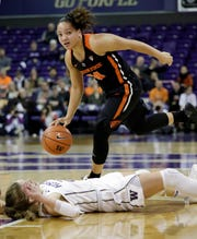 Washington's Jenna Moser tumbles to the floor after fouling Oregon State's Destiny Slocum (24) during the first half of an NCAA college basketball game Friday, Jan. 25, 2019, in Seattle.