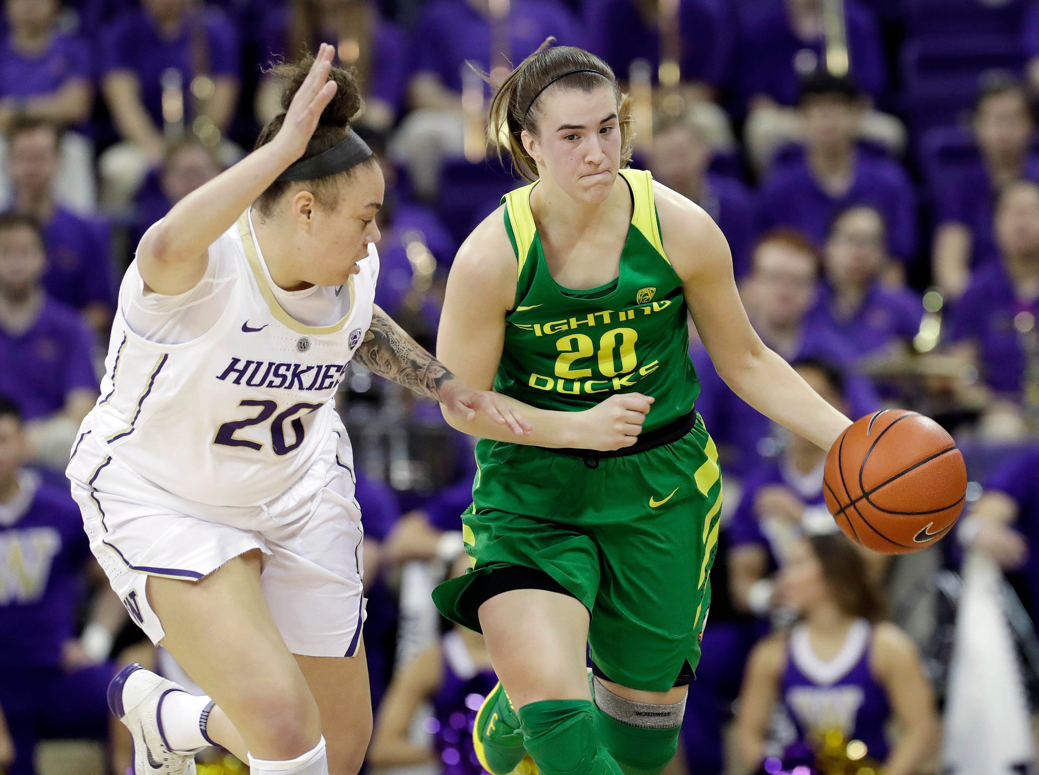 Oregon's Sabrina Ionescu, right, drives upcourt as Washington's Khayla Rooks defends in the first half of an NCAA college basketball game Sunday, Jan. 27, 2019, in Seattle.