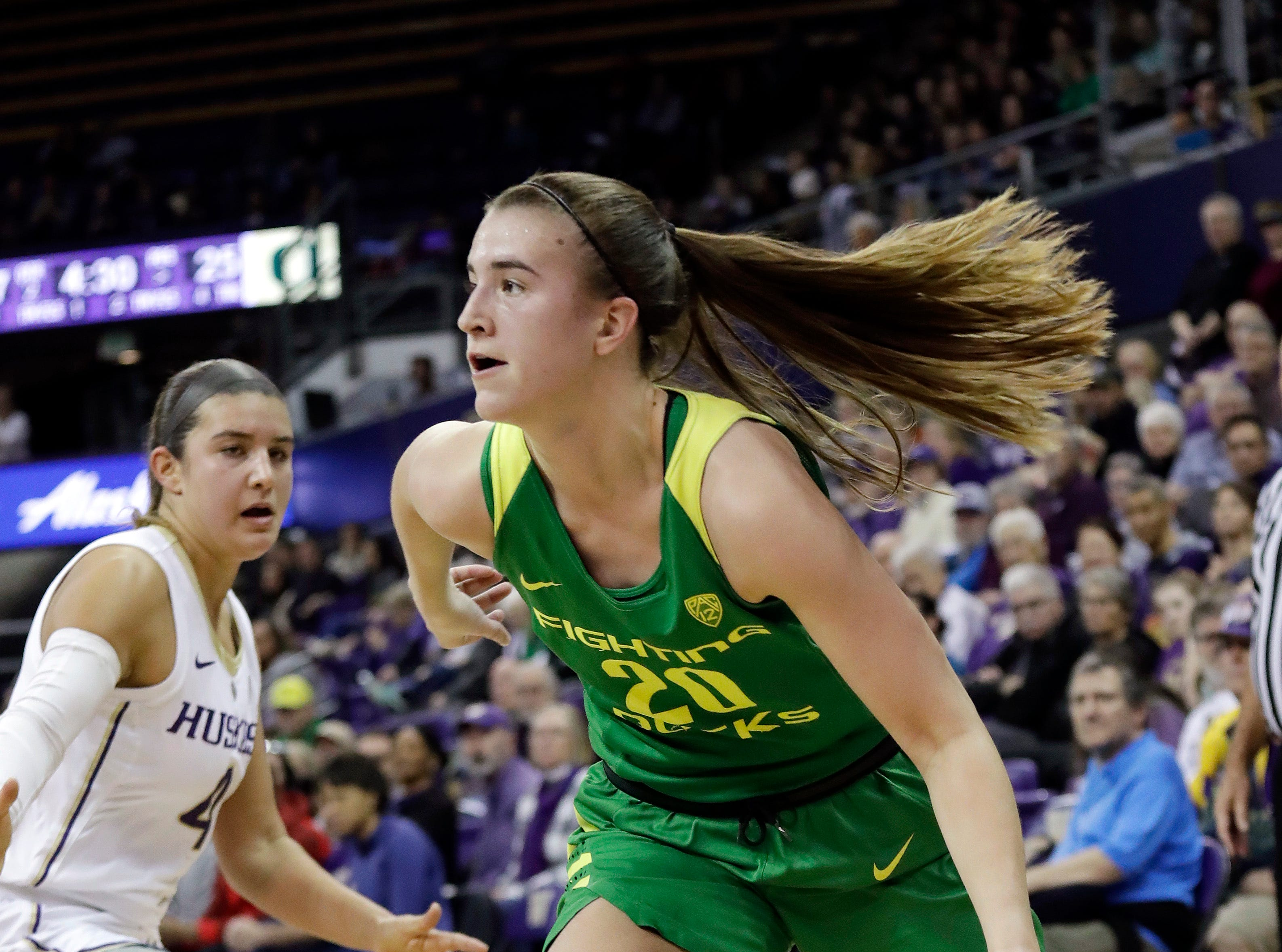 Oregon's Sabrina Ionescu, right, drives past Washington's Amber Melgoza in the first half of an NCAA college basketball game Sunday, Jan. 27, 2019, in Seattle.