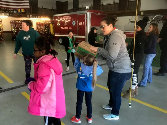 Girl Scouts, their leaders and other helpers pass boxes of cookies assembly-line fashion while unloading a truck at the Parksley Fire House on Saturday, Jan. 26, 2019 in Parksley, Virginia.