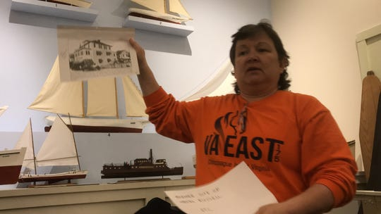Denise Bowden holds up a photograph of the Russell Hotel, formerly located on Chincoteague, Virginia, during a meeting to explore forming a town historical association, held on Thursday, Jan. 24, 2019.