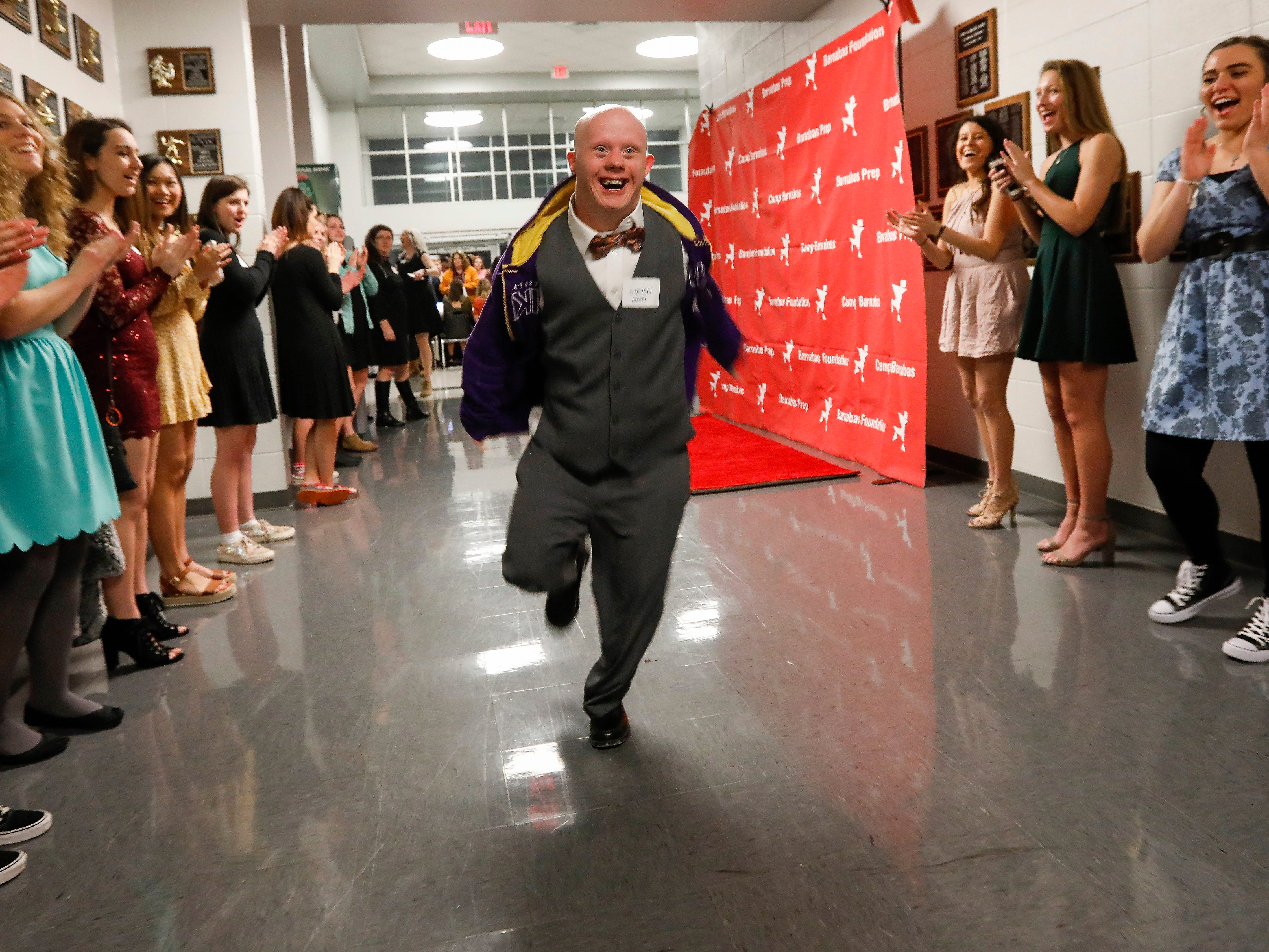 Steven smiles as he sprints down the red carpet at the Camp Barnabas Snow Ball at Springfield Catholic High School on Saturday, Jan. 26, 2019.