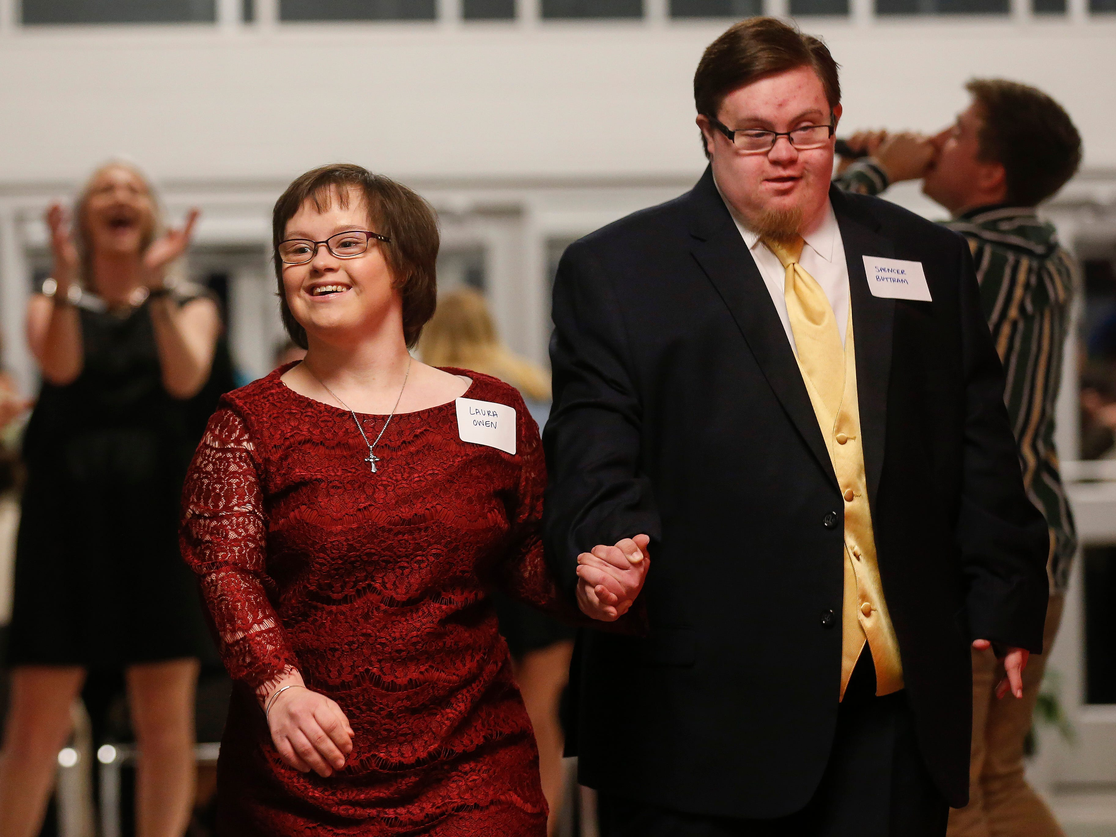 Spencer Buttram and Laura Owen walk hand-in-hand down the red carpet at the Camp Barnabas Snow Ball at Springfield Catholic High School on Saturday, Jan. 26, 2019.