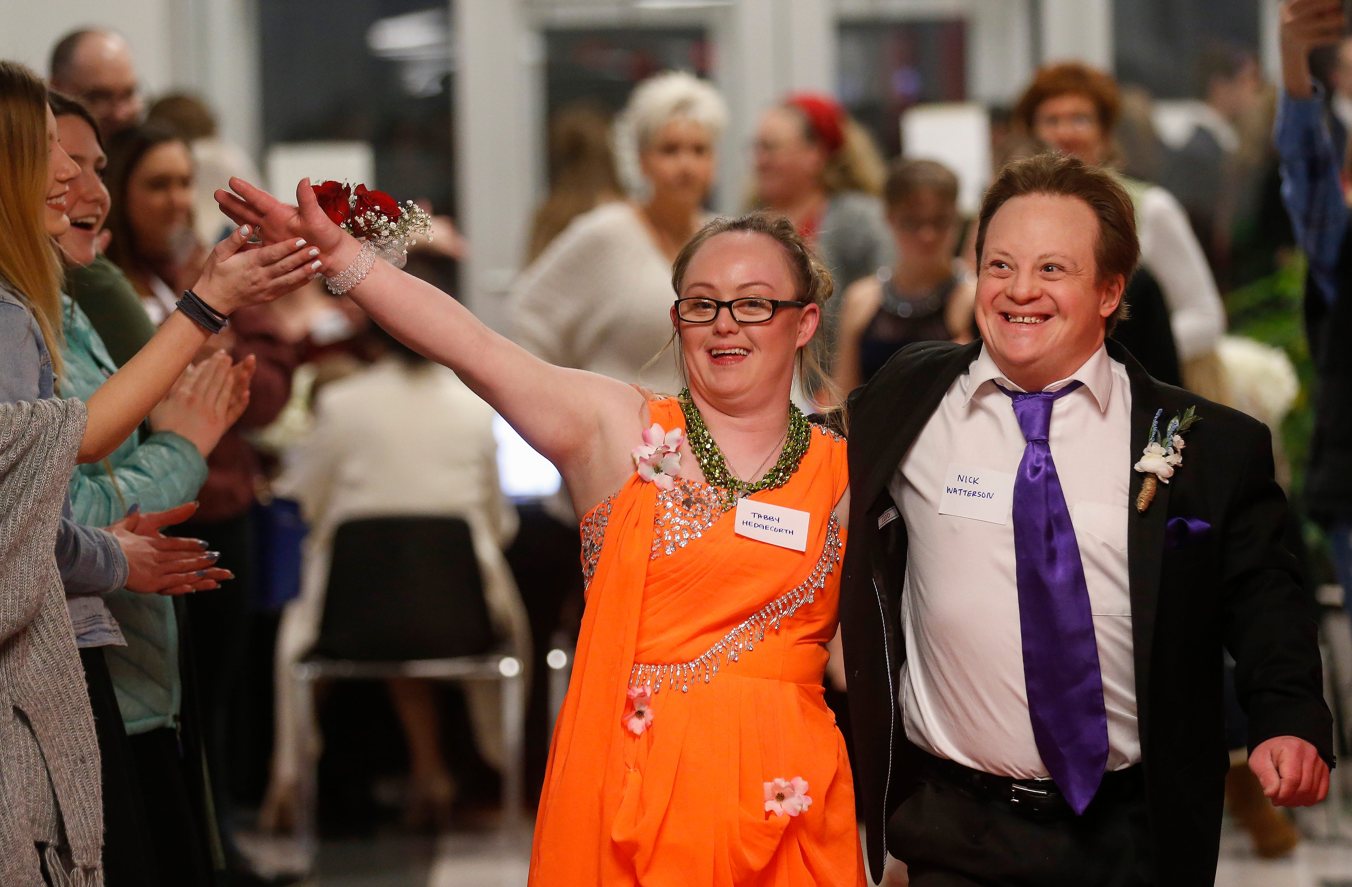 Tabby Hedgecorth and Nick Watterson smile and wave as they walk arm-in-arm down the red carpet at the Camp Barnabas Snow Ball at Springfield Catholic High School on Saturday, Jan. 26, 2019.