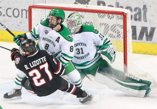 SCSU's Blake Lizotte is upended by UND's Nick Jones in front of goalie Adam Scheel in the second period on a short-handed play that resulted in a goal for the Huskies in the second period.